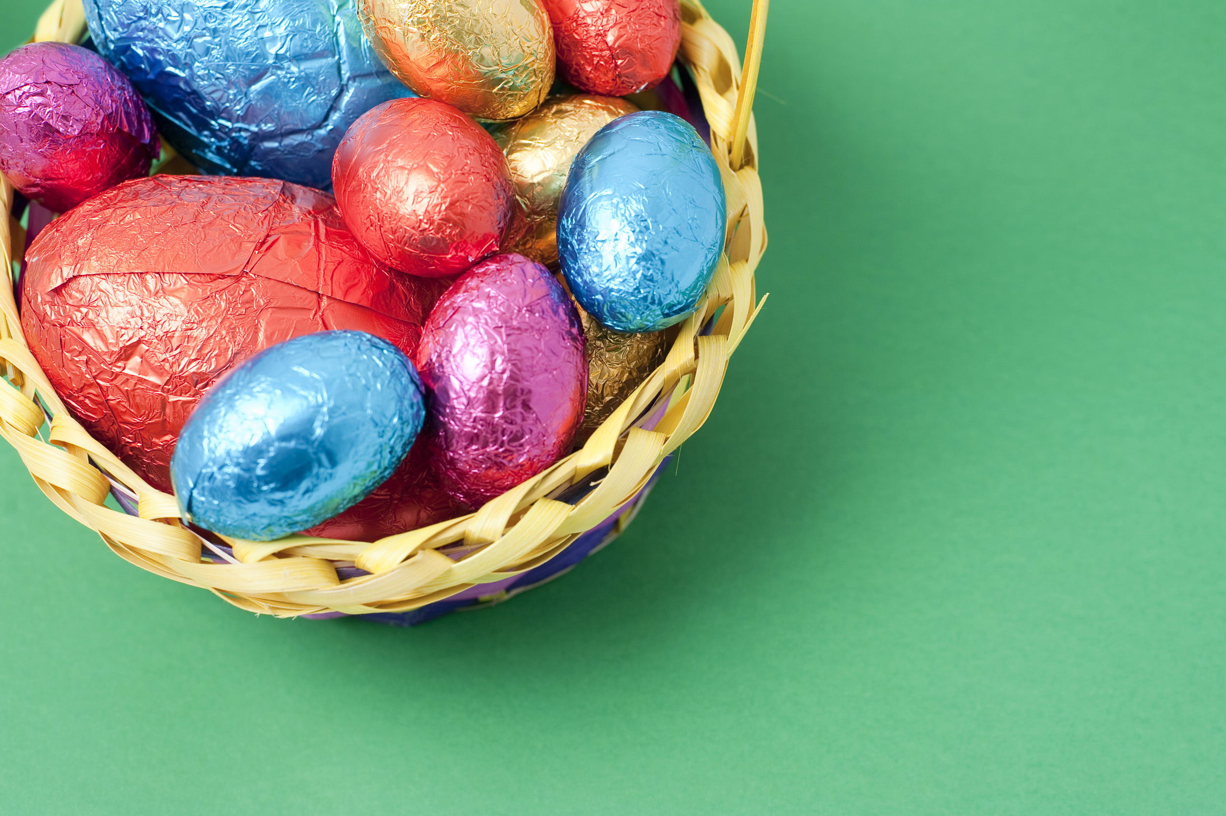 easter_copyspace.jpg - Overhead corner view of an Easter Egg basket filled with colourful foil wrapped eggs with copyspace