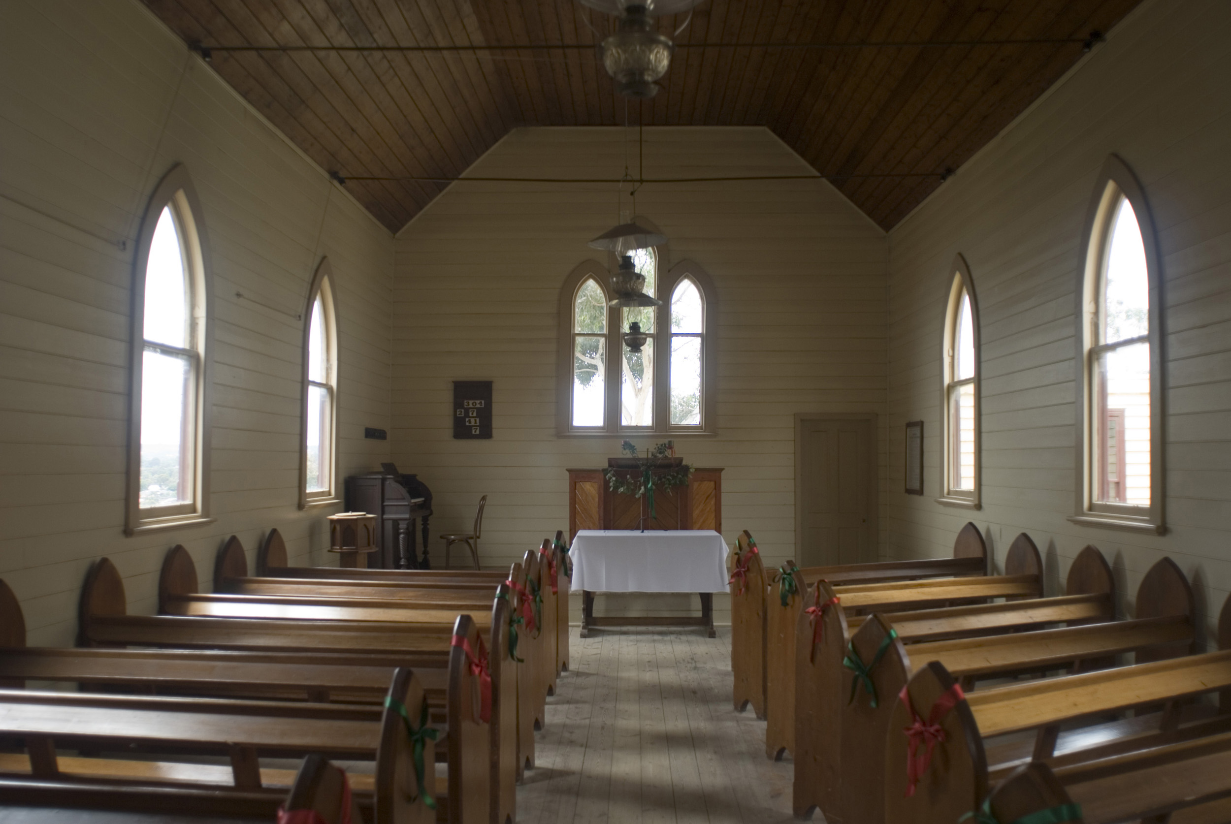 church_aisle.jpg - Aisle in rural church lined with old wooden pews leading to a simple altar