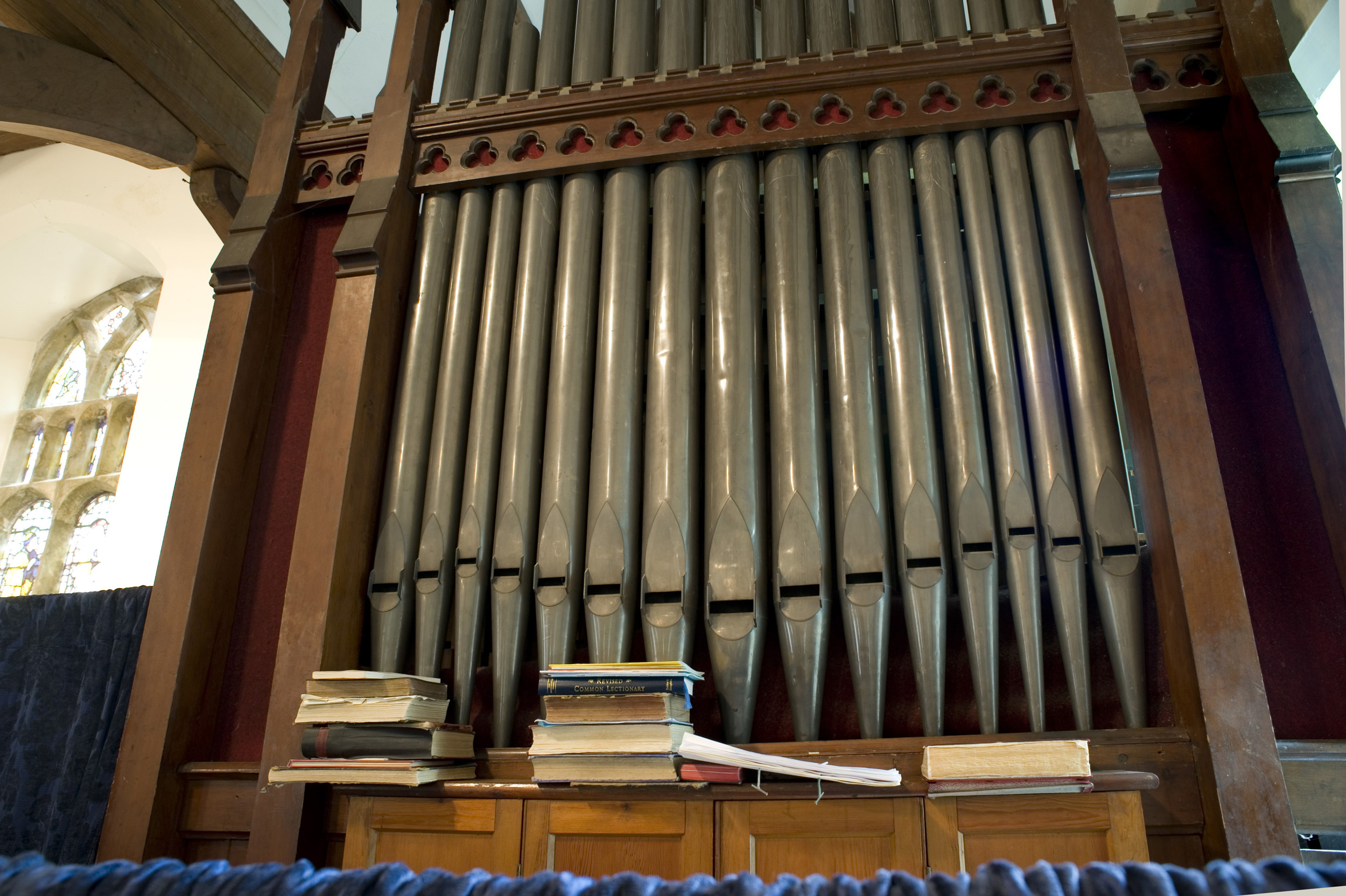 church_organ_pipes.jpg - Tall church organ pipes mounted in a wooden frame surround in a small country church