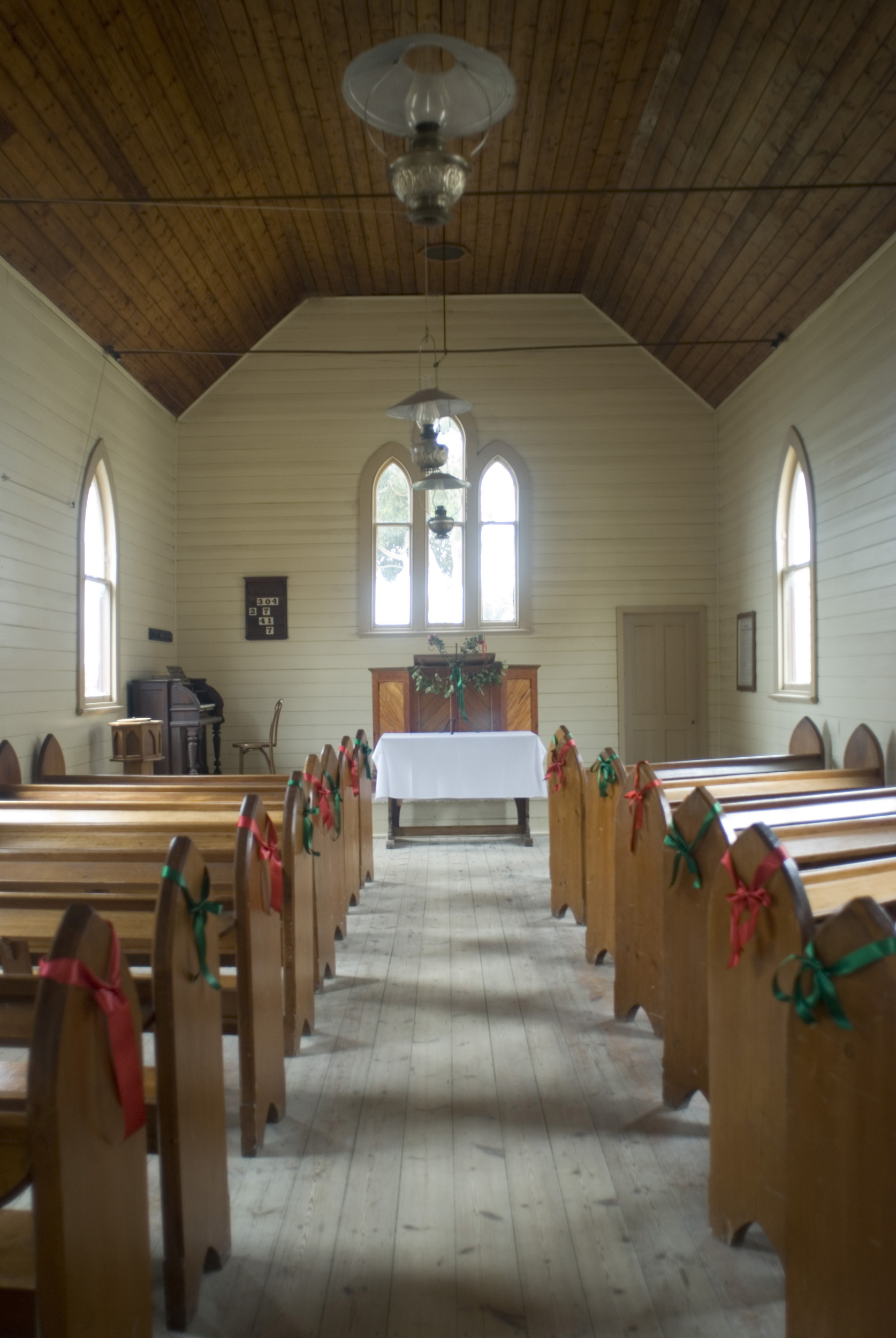 small_historic_church.jpg - Small historic church interior looking down the stone aisle past the wooden pews to the simple alter at the opposite end - non commerical use only
