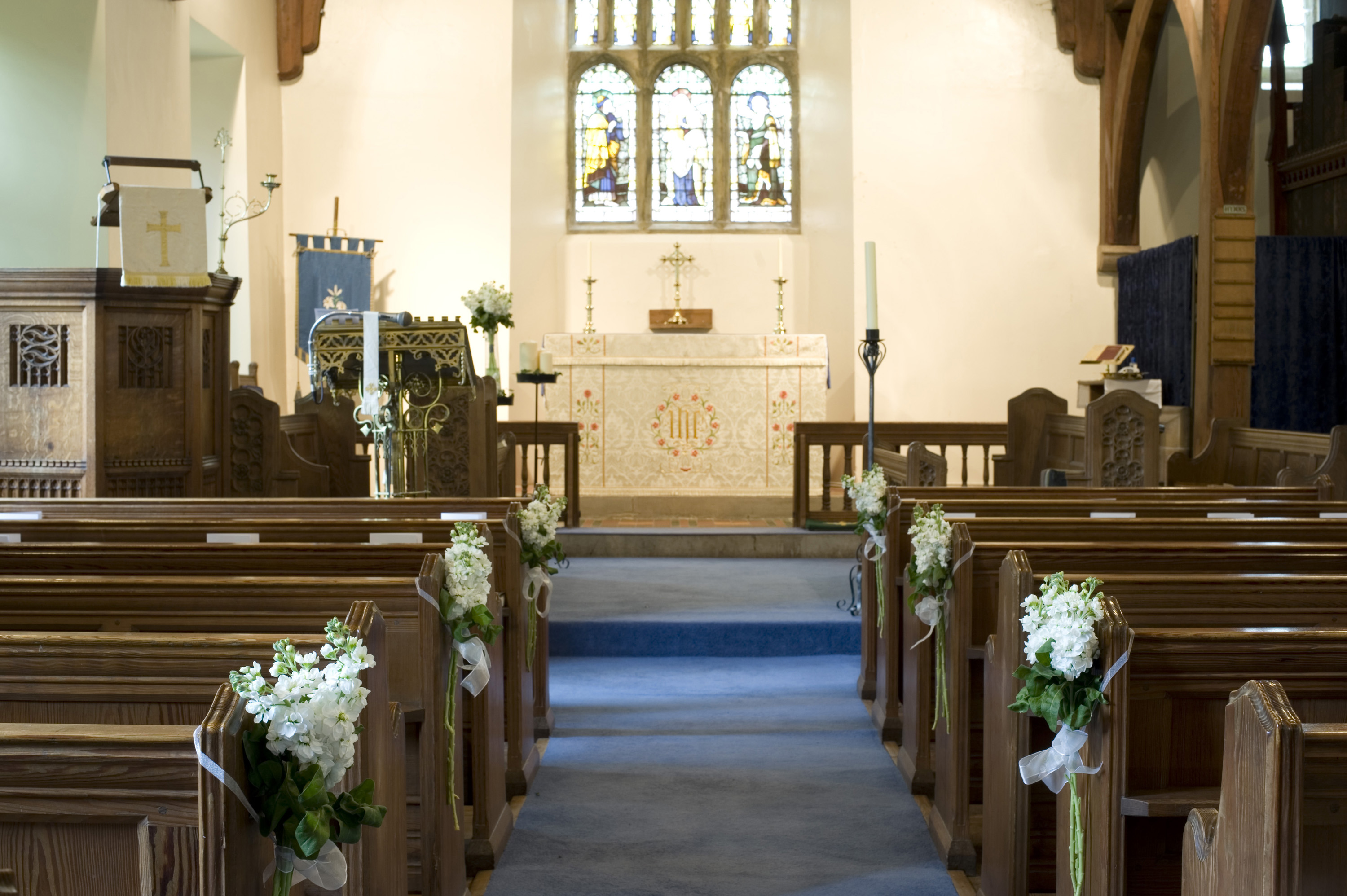 spring_time_church.jpg - Springtime church aisle with wooden pews decorated with white spring blossom in a small country church