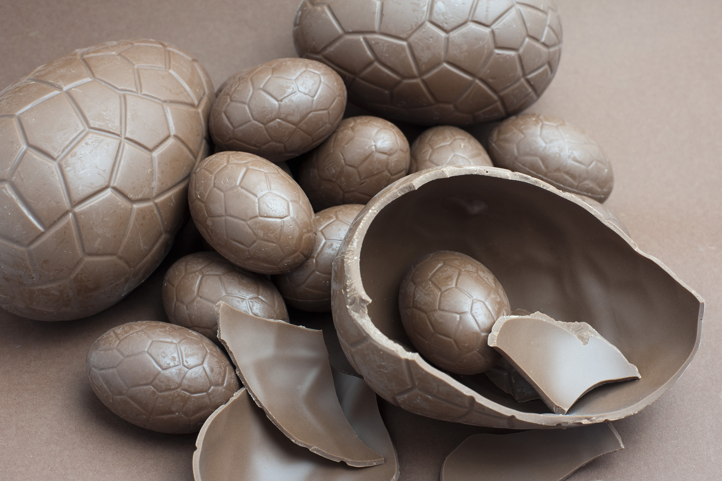 broken_easter_egg.jpg - Collection of various sized chocolate Easter Eggs with one large broken one in the foreground