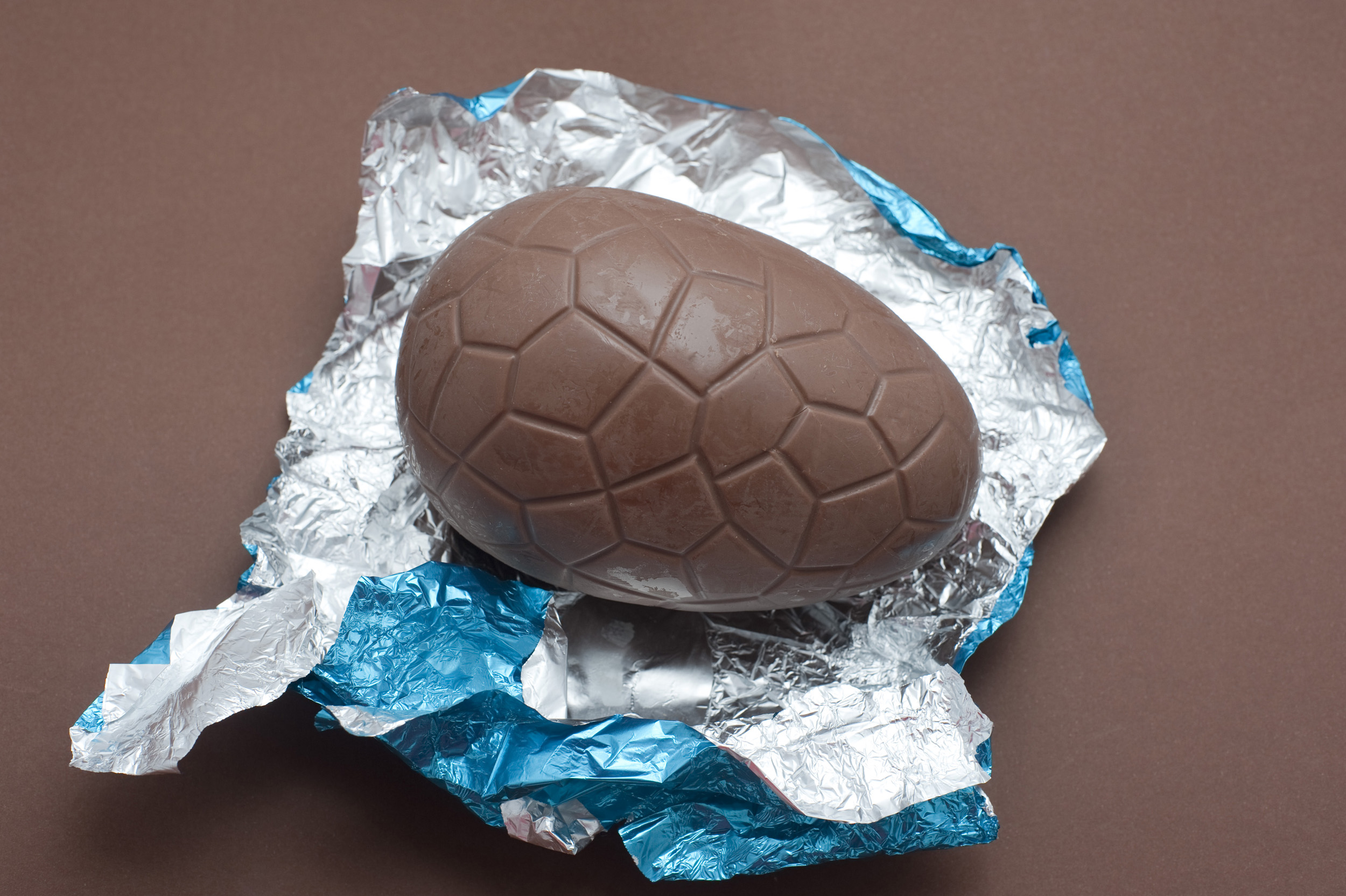 chocolate_egg.jpg - Single unwrapped chocolate Easter Egg sitting on its colourful shiny silver and blue foil wrapper on a brown background