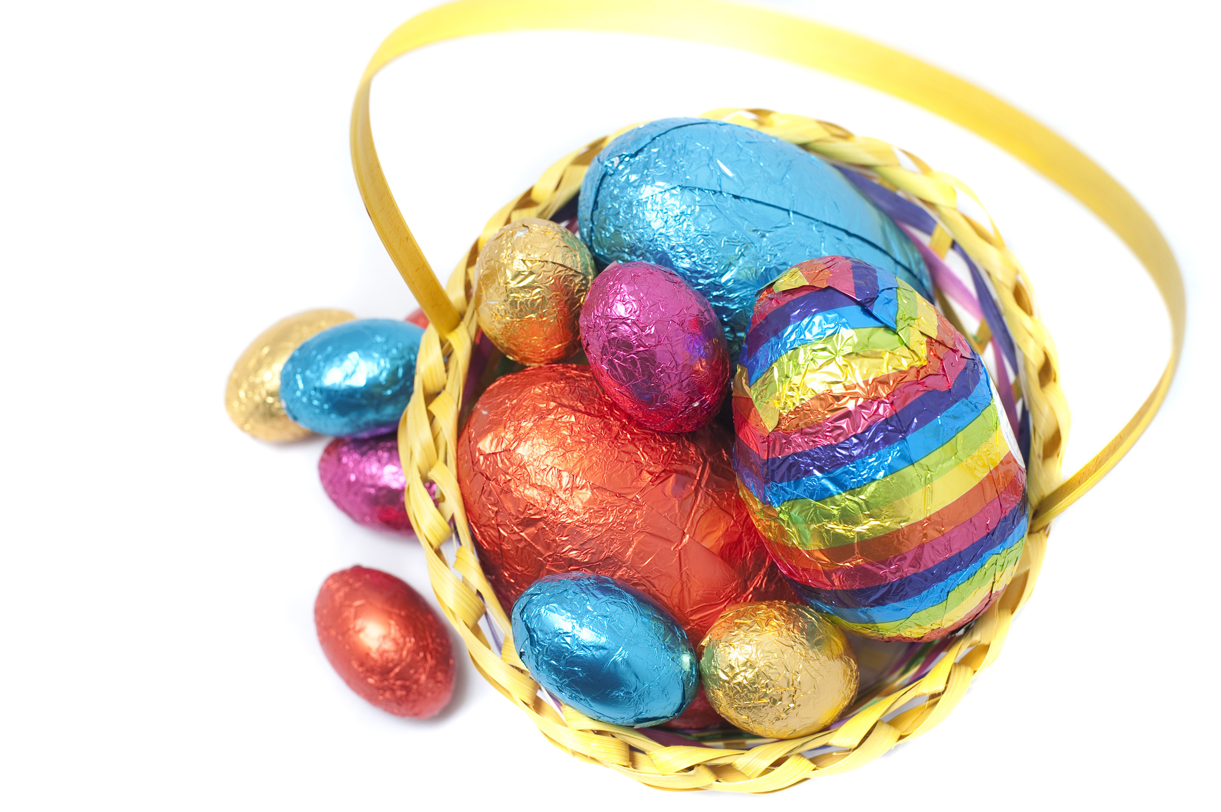 colored_easter_eggs.jpg - High angle view of a decorative basket of different sized colored Easter Eggs in shiny foil wrapping