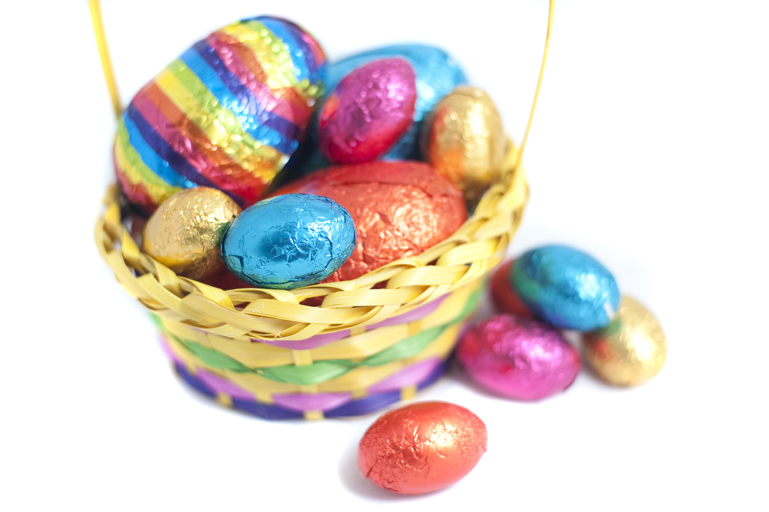colorful_easter_basket.jpg - Colourful Easter basket filled with multicolour foil wrapped eggs on a white studio background