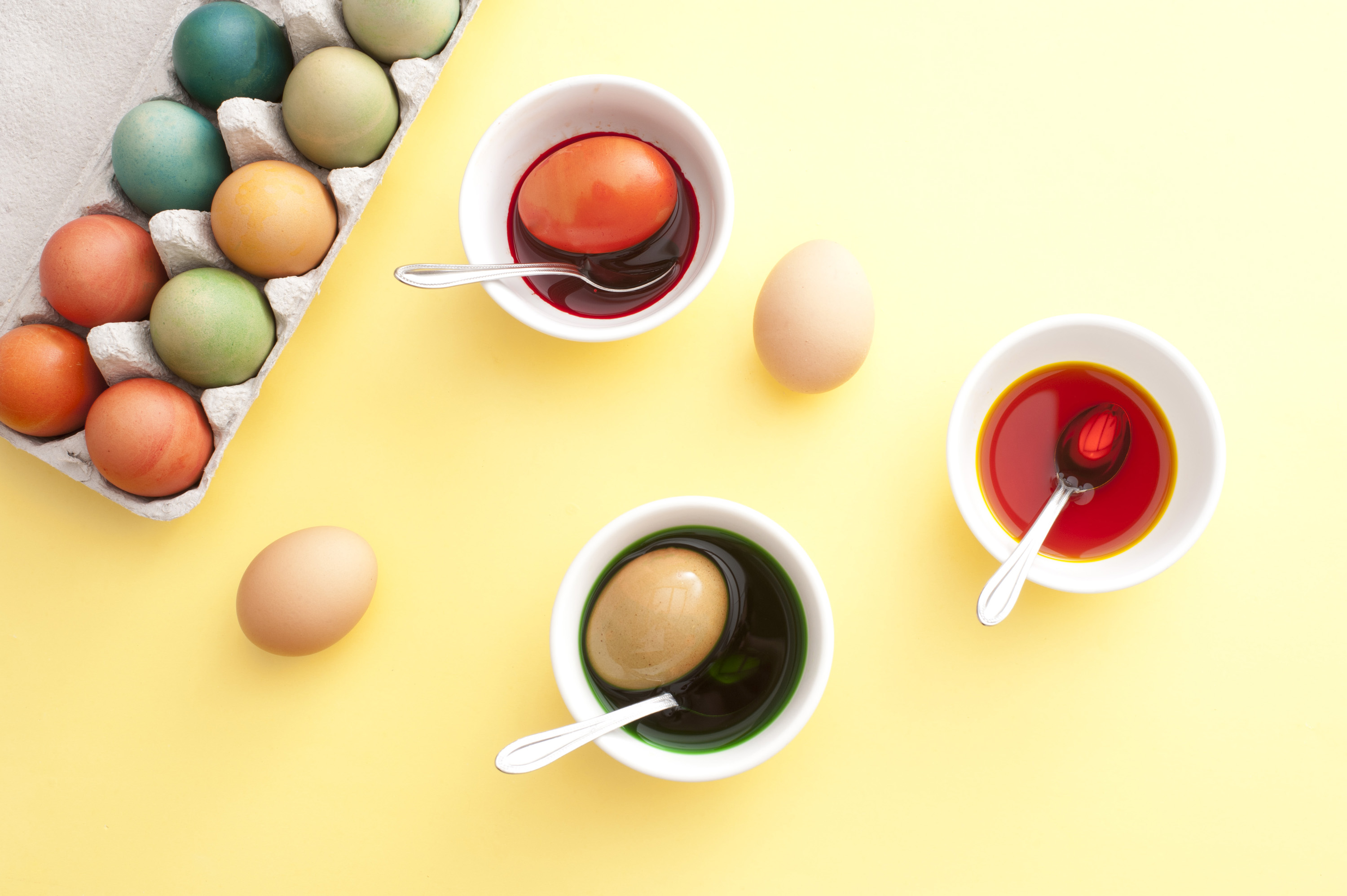 colouring_eggs.jpg - Overhead view of three bowls filled with dye beside a carton filled with colorful eggs