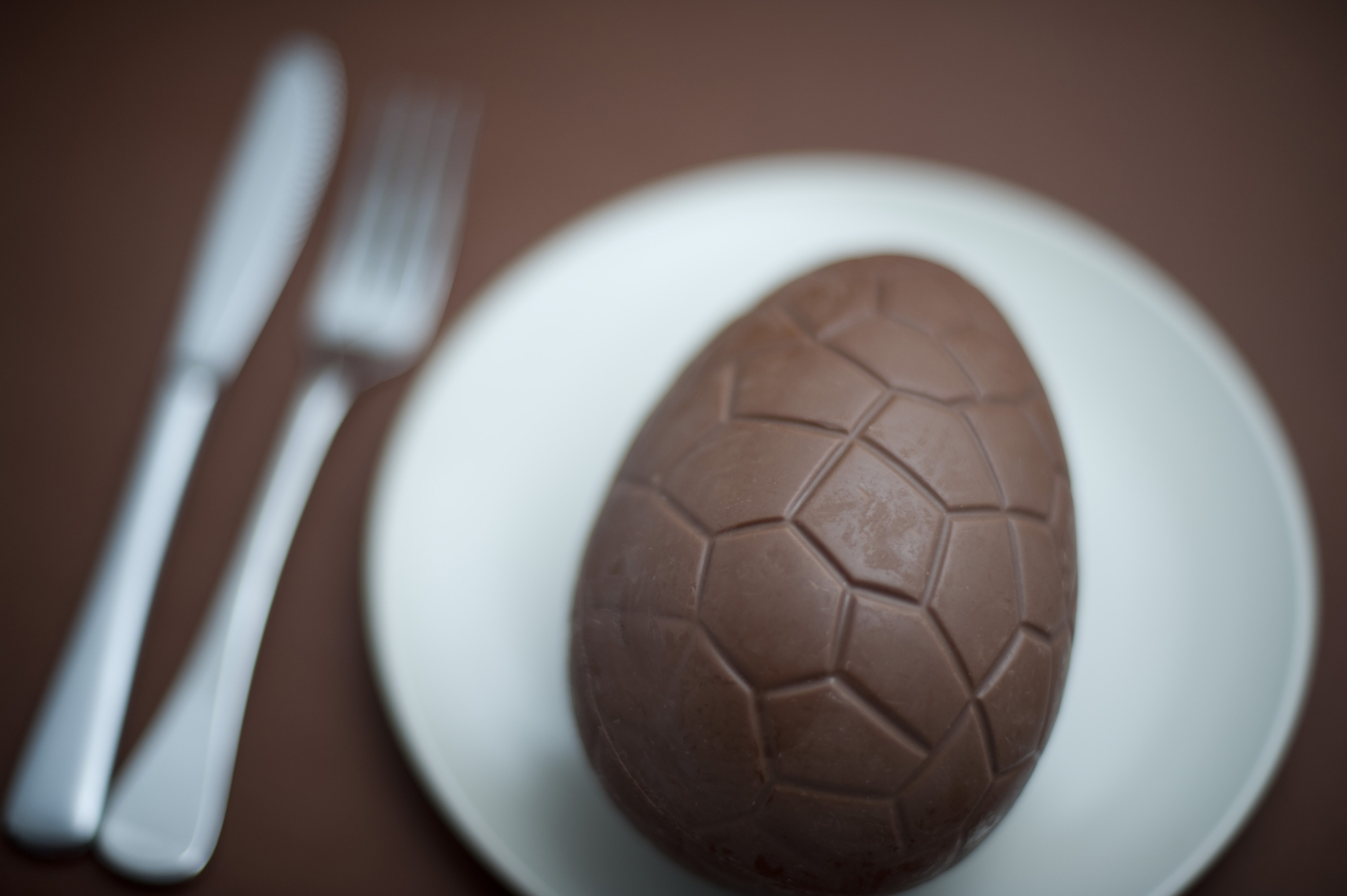 concept_chocolate_egg.jpg - Overhead close up view of one chocolate egg in small white bowl with fork and knife nearby