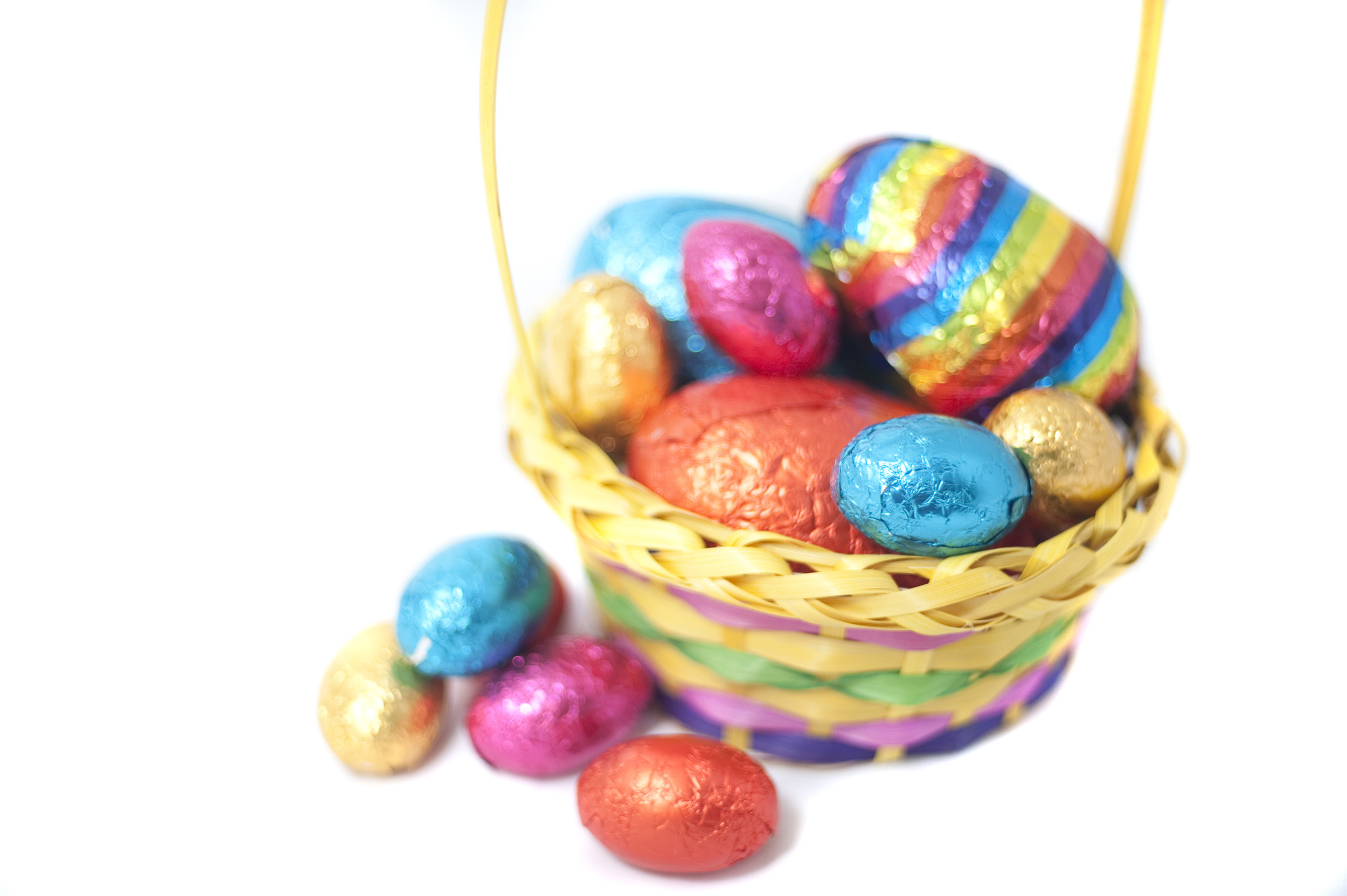easter_basket_of_eggs.jpg - Easter Basket filled with an assortment of different sized colourful foil wrapped eggs with copyspace
