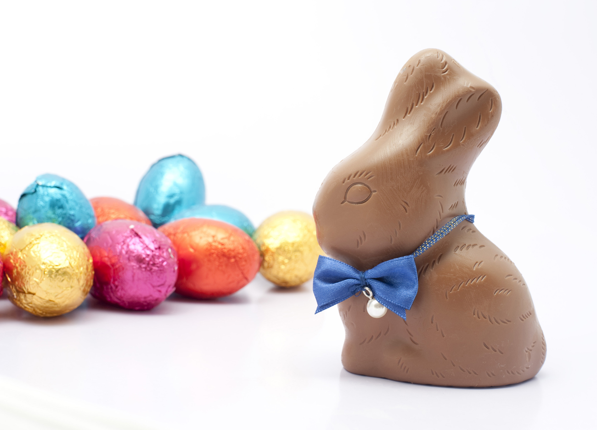 easter_bunny_eggs.jpg - Chocolate Easter bunny wearing a cute bow tie watching over a pile of colourful small Easter eggs