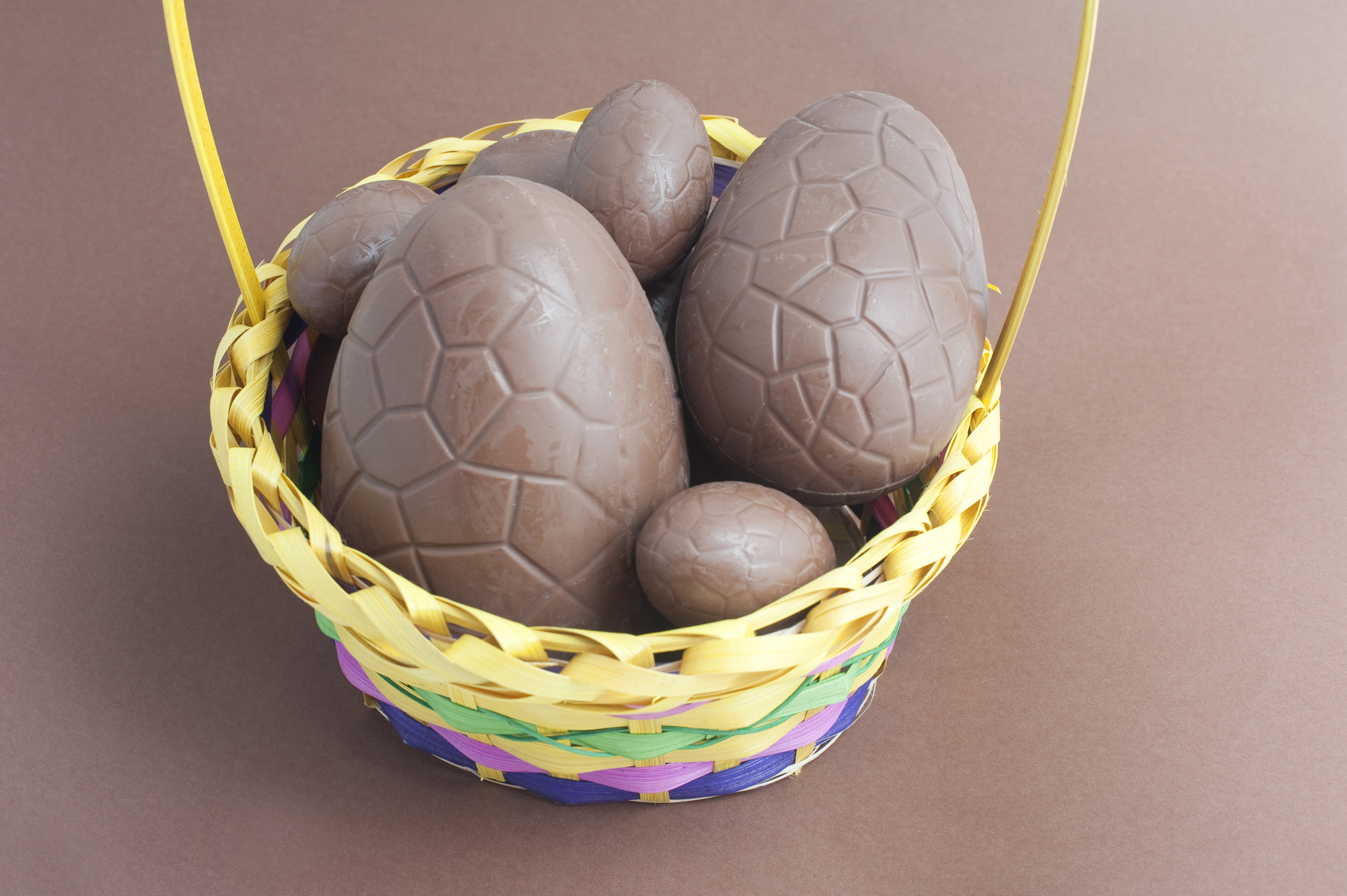 easter_chocolate_basket.jpg - Decorative basket filled with milk chocolate Easter Eggs on a brown background