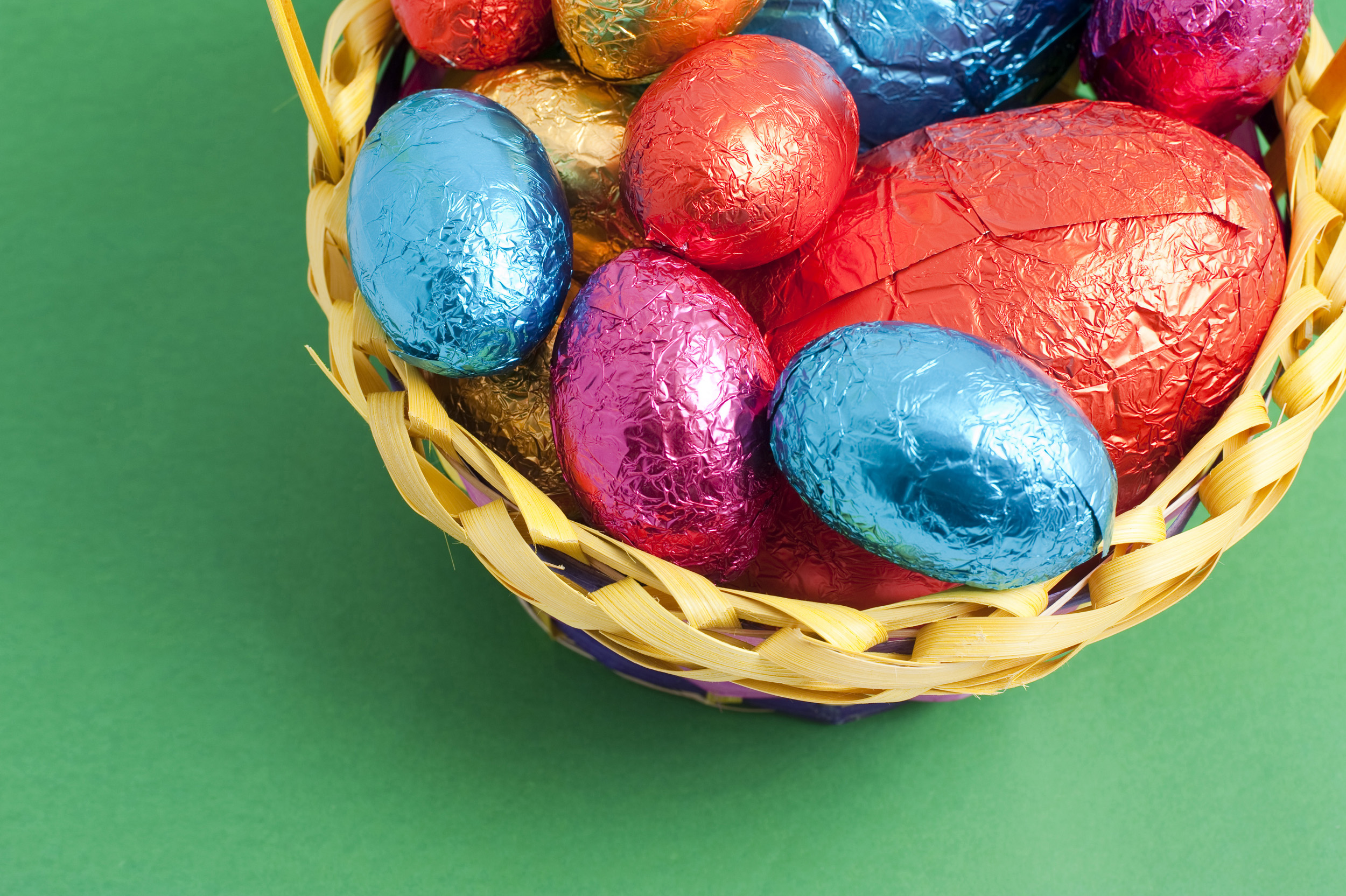 easter_corner.jpg - Corner of colourful Easter Eggs of varying sizes in shiny foil wrapping collected in a wicker basket