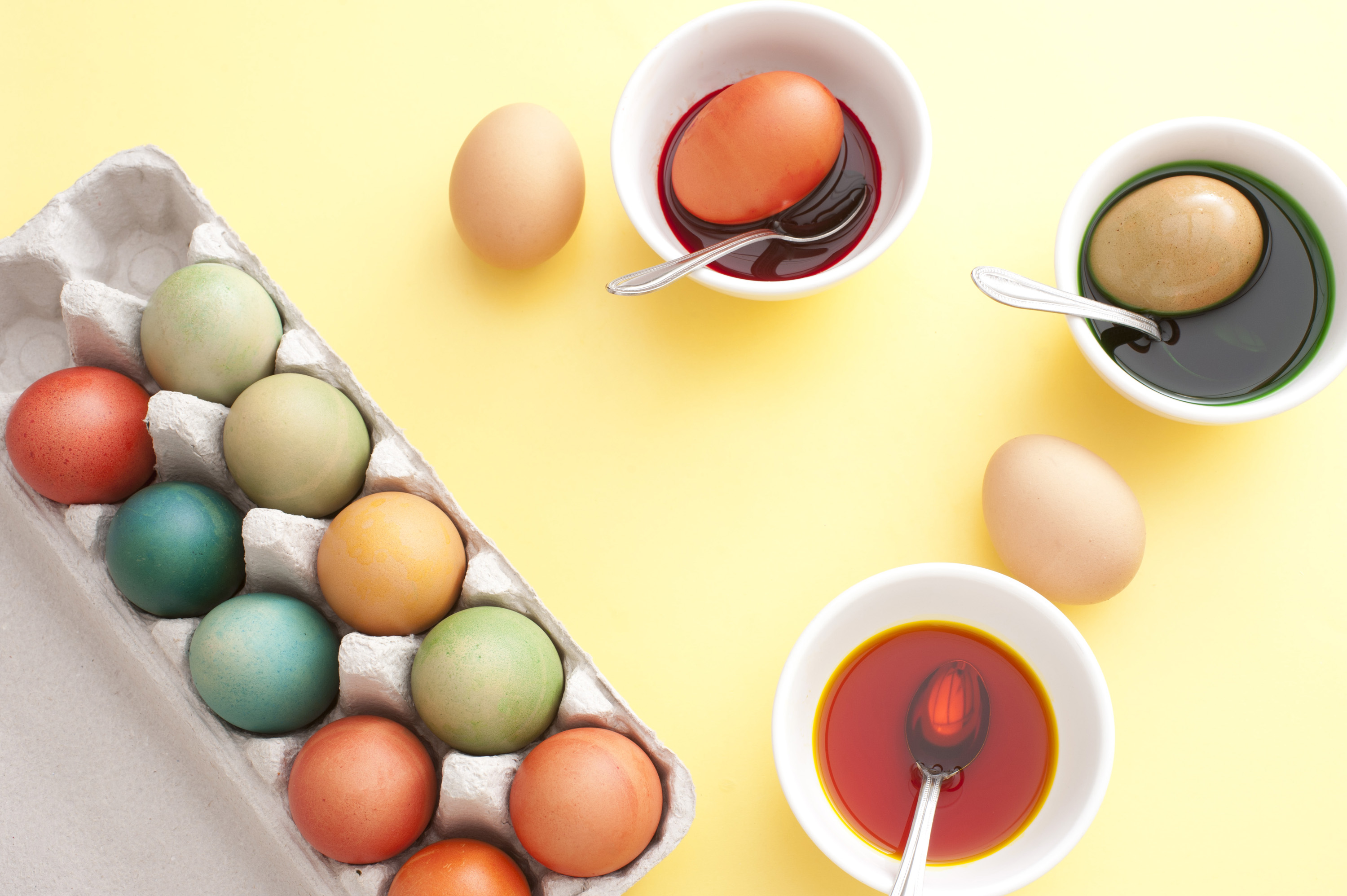 easter_egg_preparing.jpg - Childhood tradition dyeing boiled eggs for a festive Easter with an overhead view of bowls of dye and a cardboard box full of dyed completed eggs on a yellow background