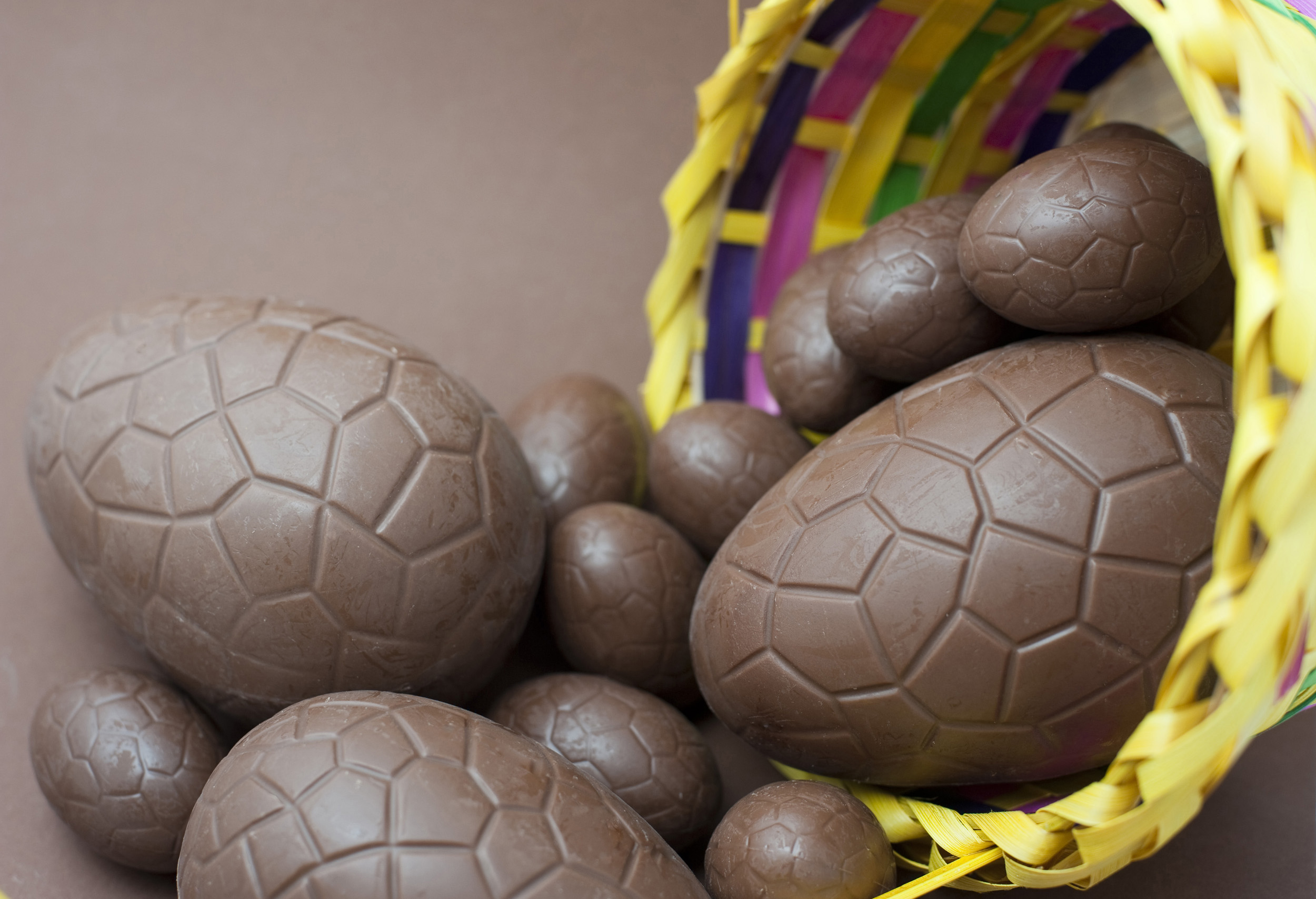 easter_egg_selection.jpg - Easter Egg selection of various sized milk chocolate eggs spilling out of a decorative basket onto a brown background