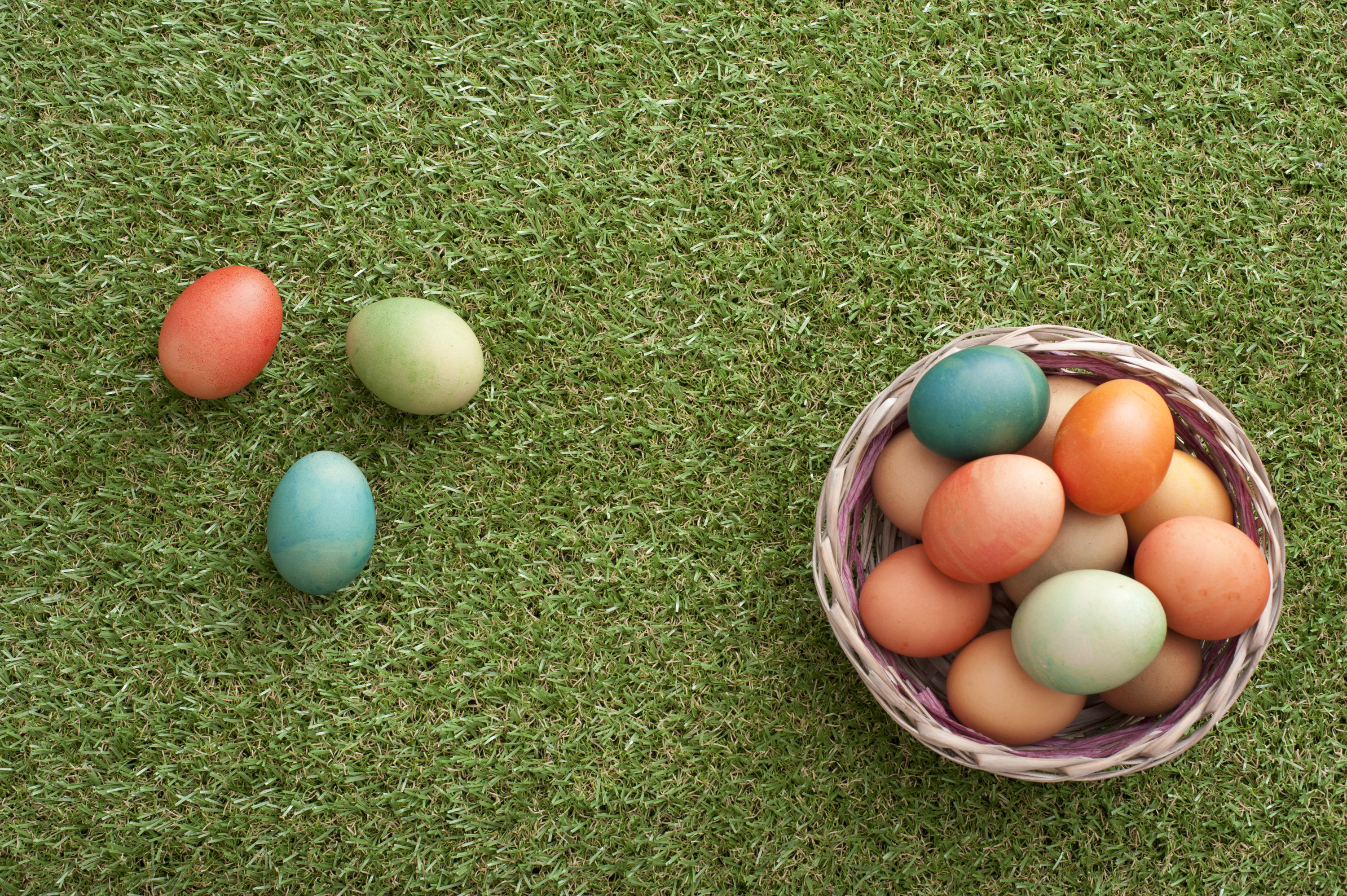 easter_eggs_hunt.jpg - Overhead view of three colorful Easter eggs in grass beside woven basket filled with more of them