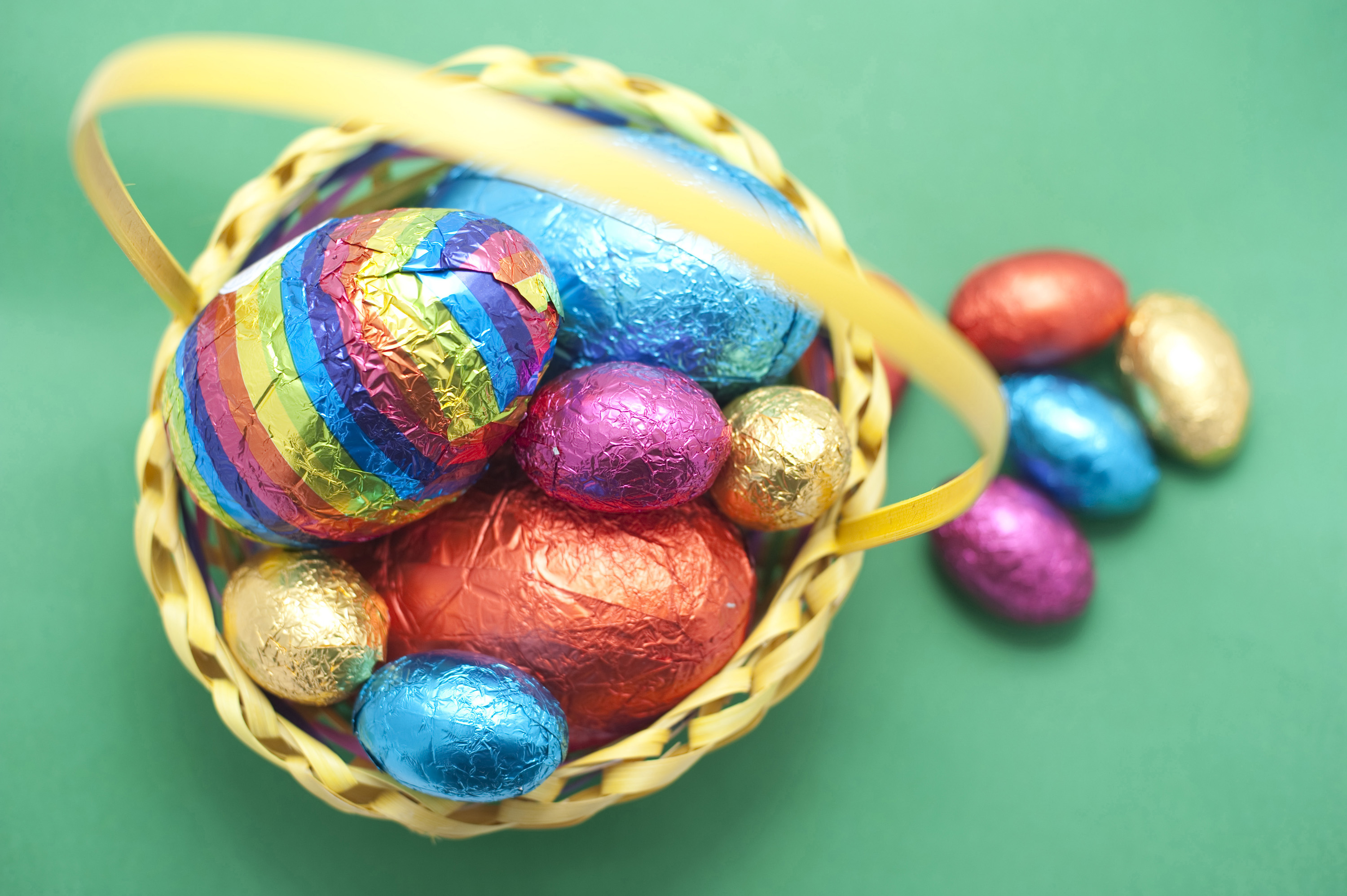egg_basket.jpg - Colorful chocolate Easter Egg basket with a collection of different sized and coloured eggs on a green background