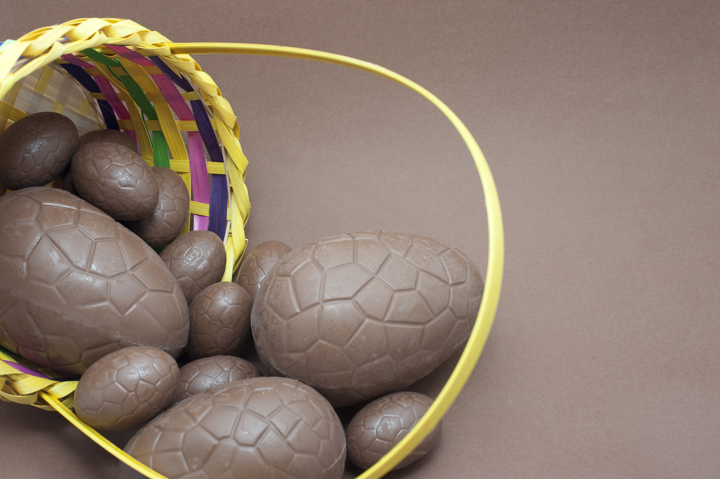 milk_chocolate_eggs.jpg - Milk chocolate Easter Eggs spilling out of a basket onto a brown background with copyspace