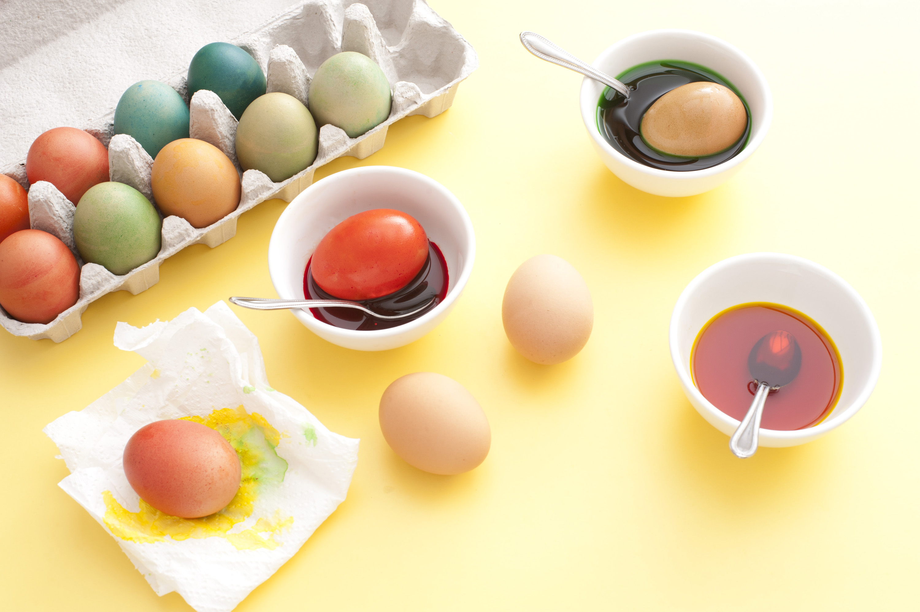 pace_egg_colouring.jpg - From above view of several painted Easter eggs in box and process of dyeing with different colors using bowls and spoons, over yellow table background