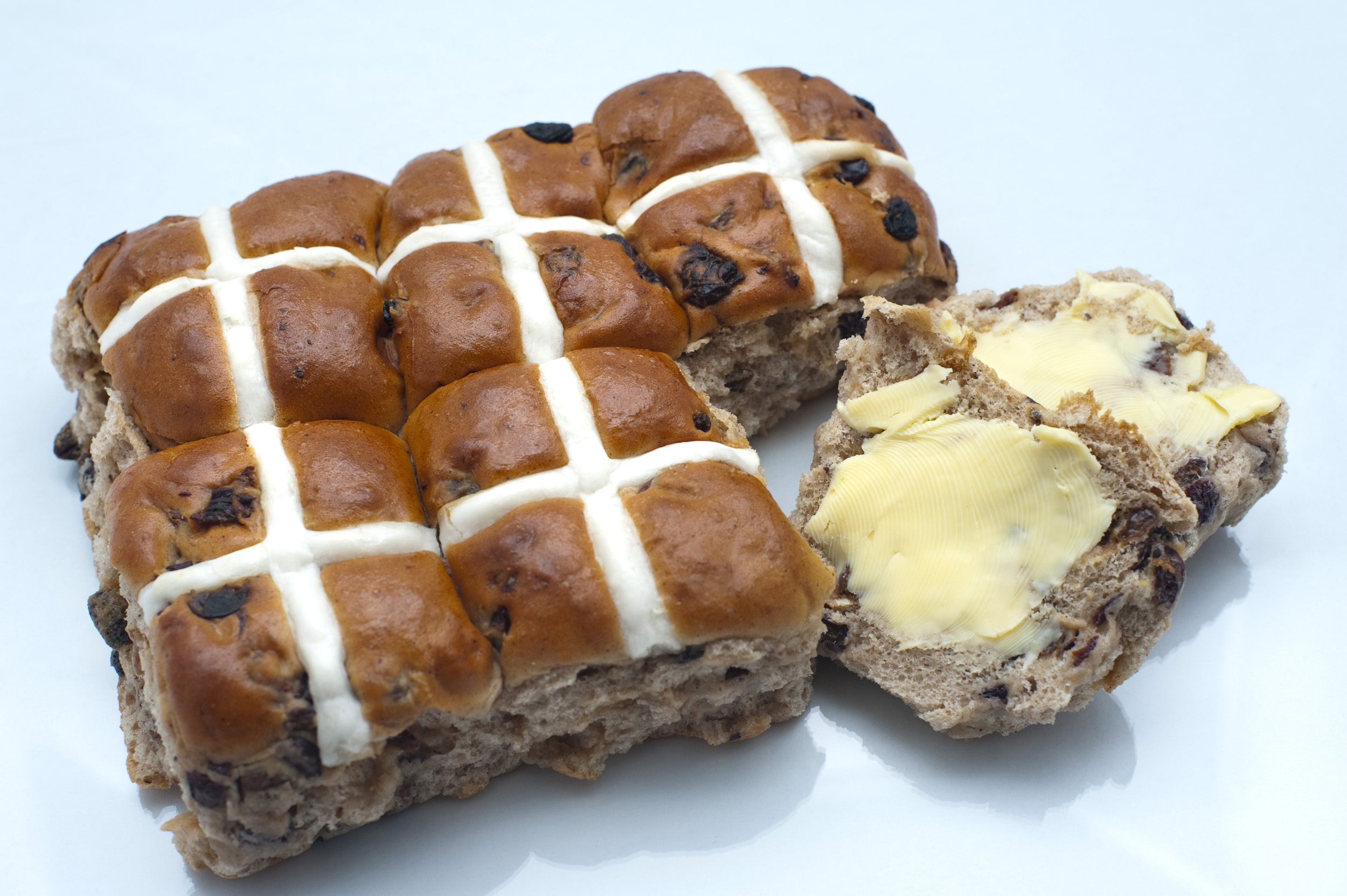 butter_hotcross_bun.jpg - Overhead view of a batch of fresh Easter Hot Cross Buns showing the glazed cross with one sliced and buttered one to the side