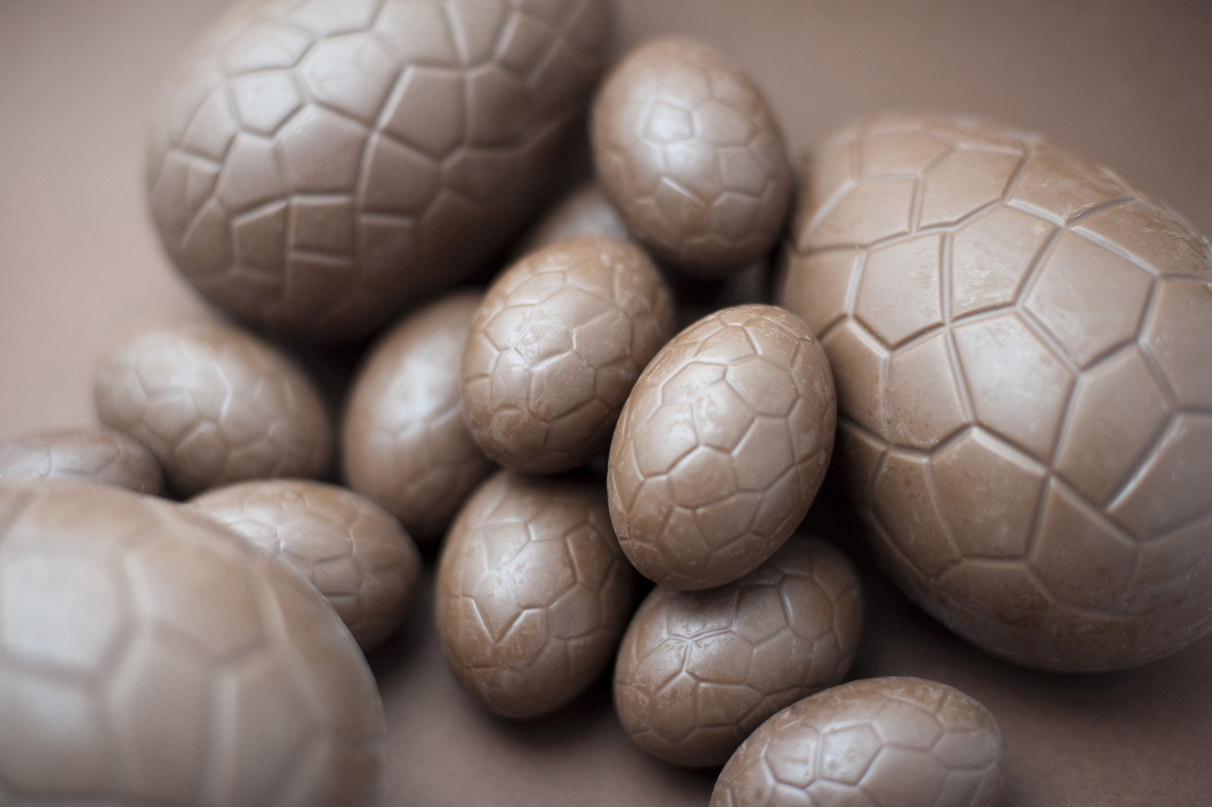 chocolate_eggs.jpg - Assorted unwrapped milk chocolate Easter Eggs of different sizes on a brown background