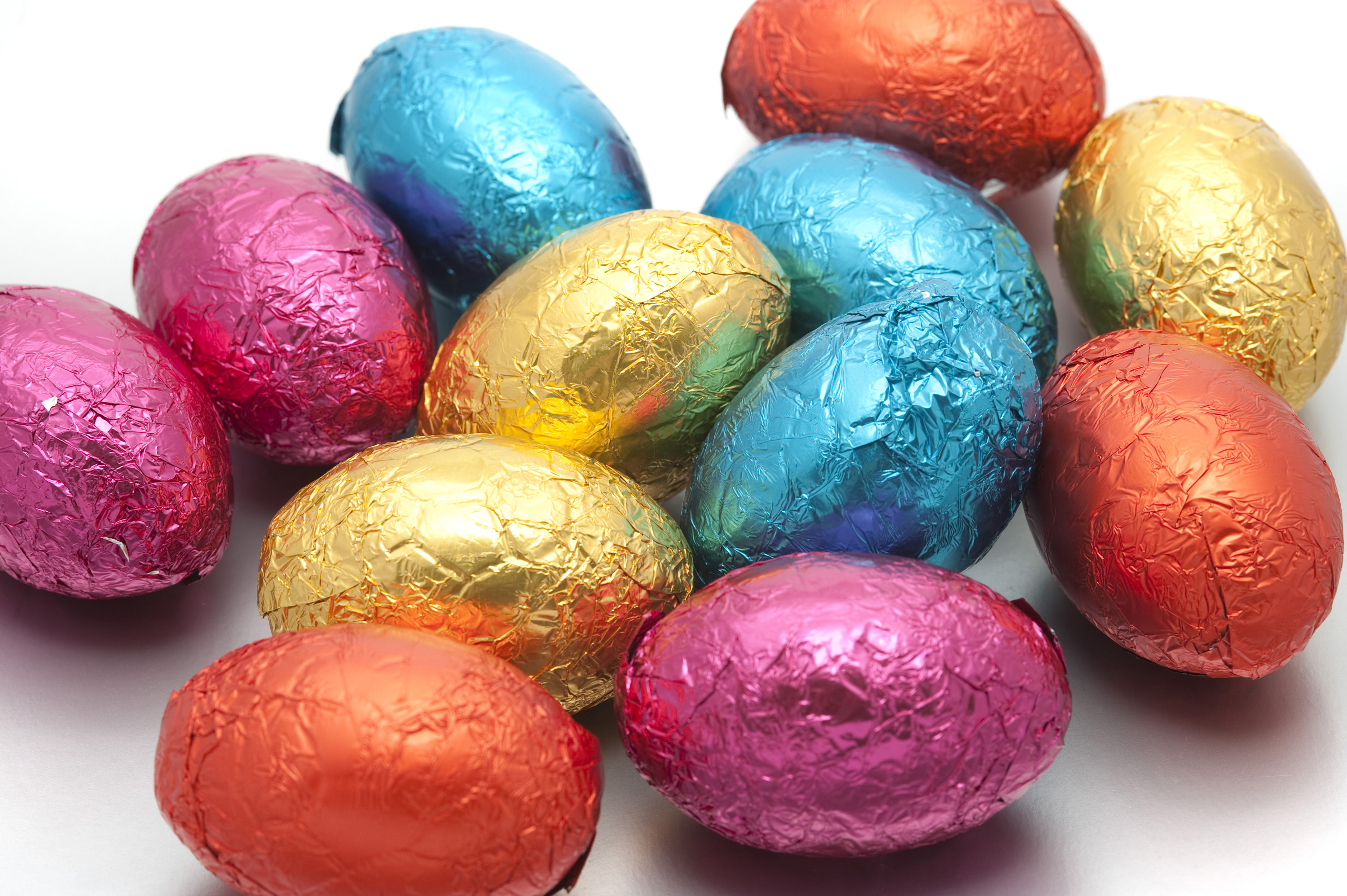 easter_egg_colors.jpg - Collection of multicoloured Easter Eggs wrapped in different coloured shiny foil wrappers spread out randomly