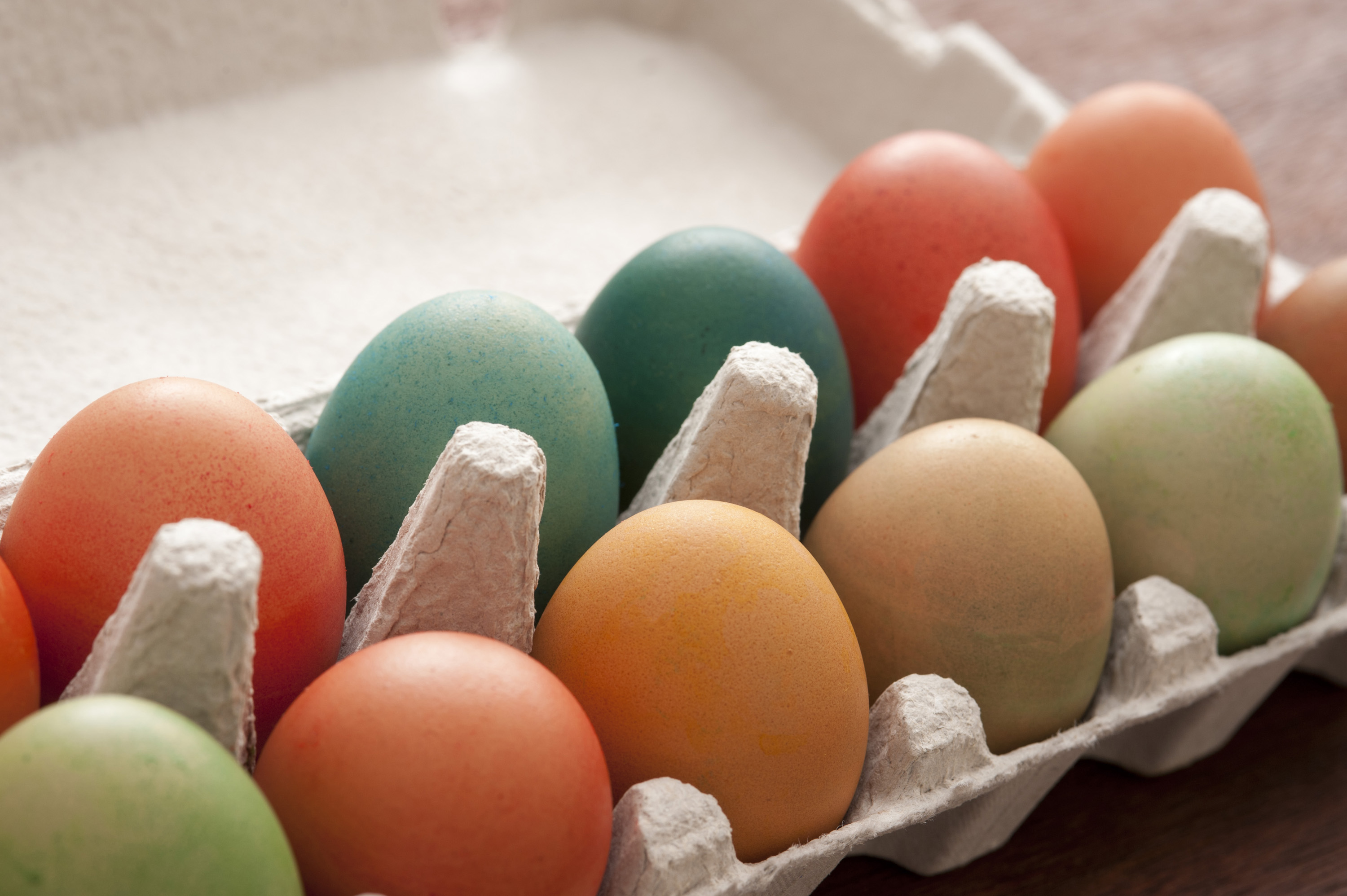 easter_real_eggs.jpg - Cardboard carton of colorful dyed Easter eggs homemade in the old tradition in a close up view with copy space for your seasonal greeting