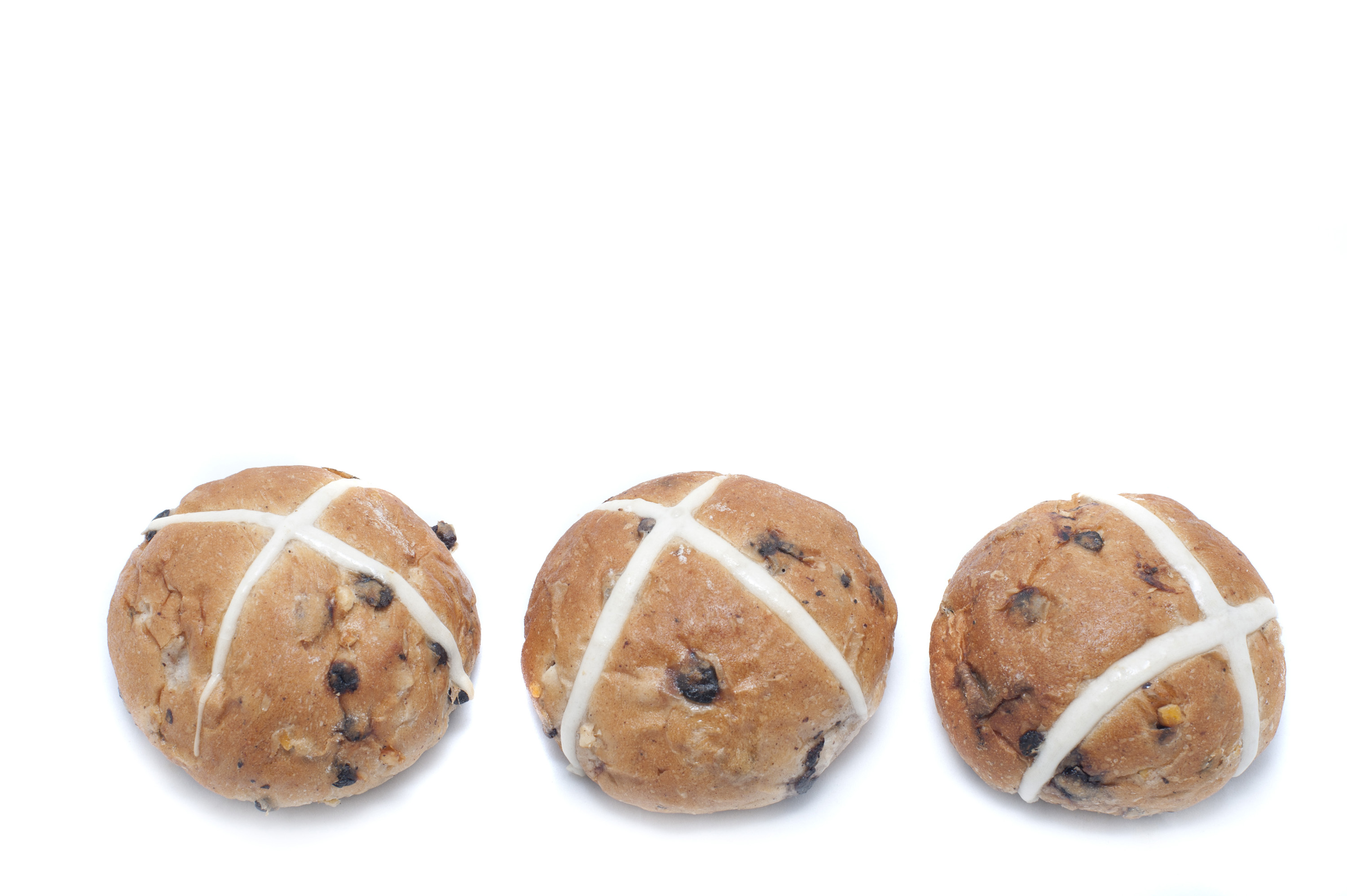 three_hot_cross_buns.jpg - Border of three freshly baked fruity spicy Hot Cross Buns on a white background with copy space for your seasonal greeting