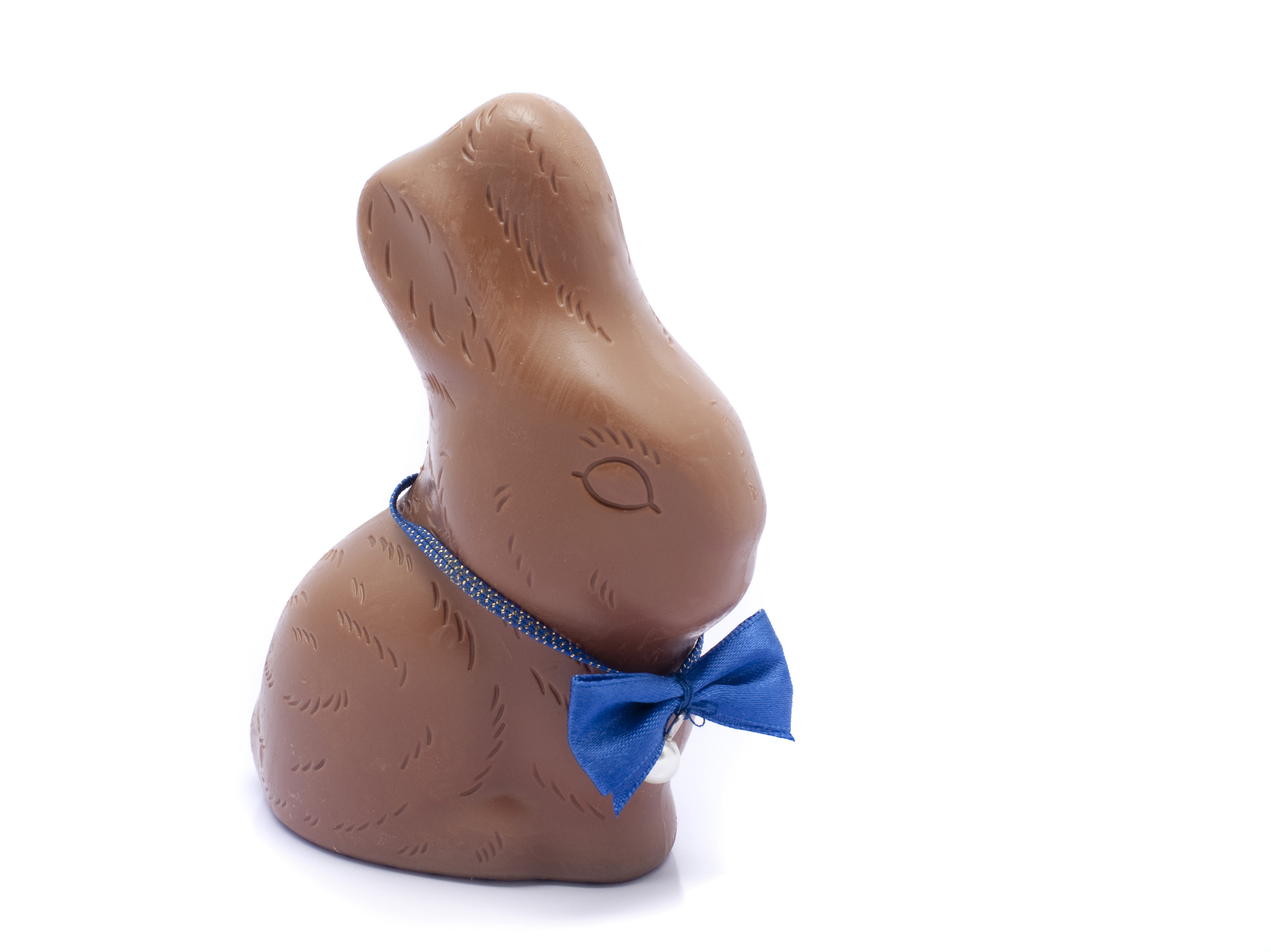 easter_chocolate_rabbit.jpg - Milk chocolate Easter rabbit egg wearing a cute blue bow tie on a white background
