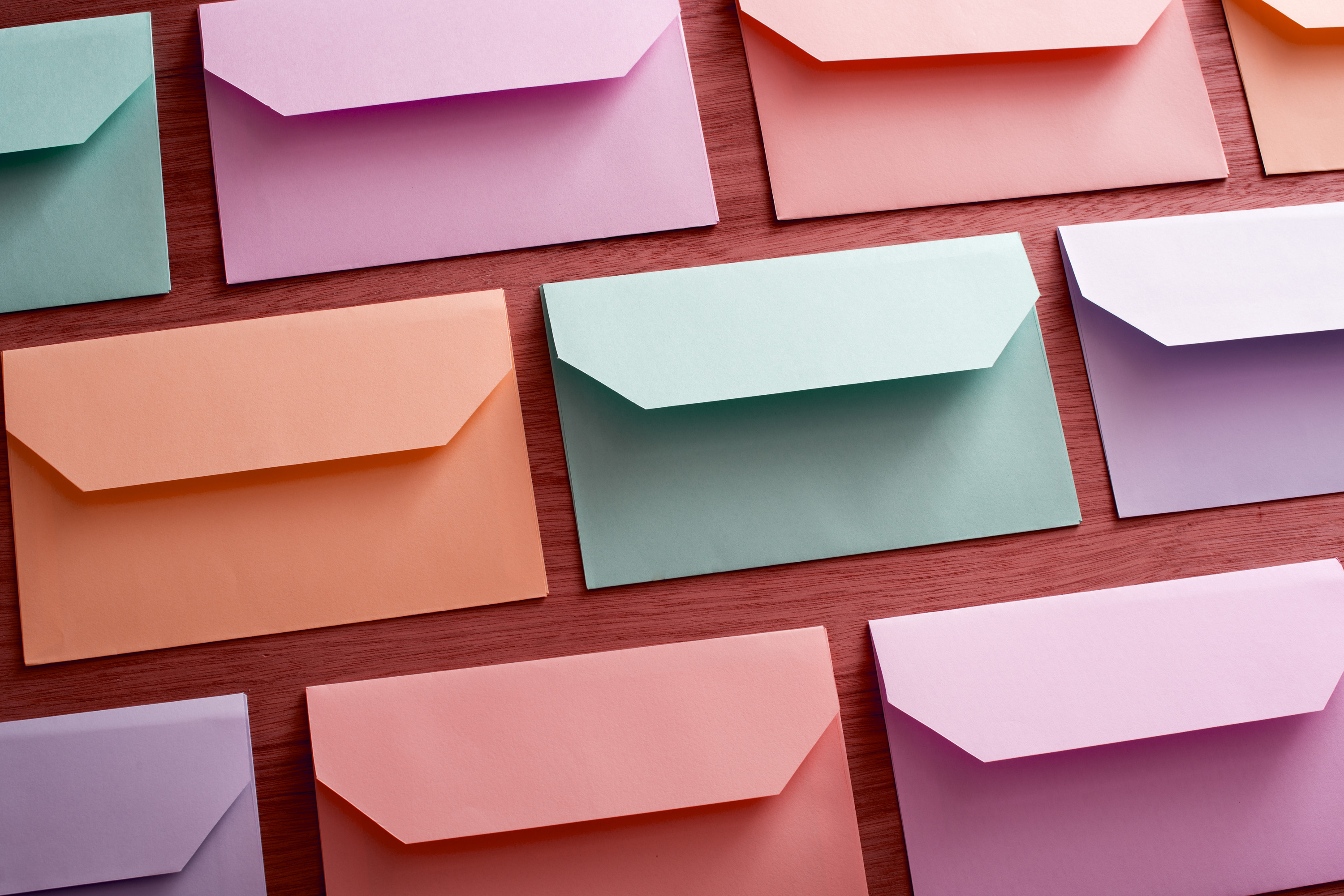 easter_colour_envelopes.jpg - Background of colorful envelopes for Easter messages arranged neatly in rows face down on wood in a full frame view