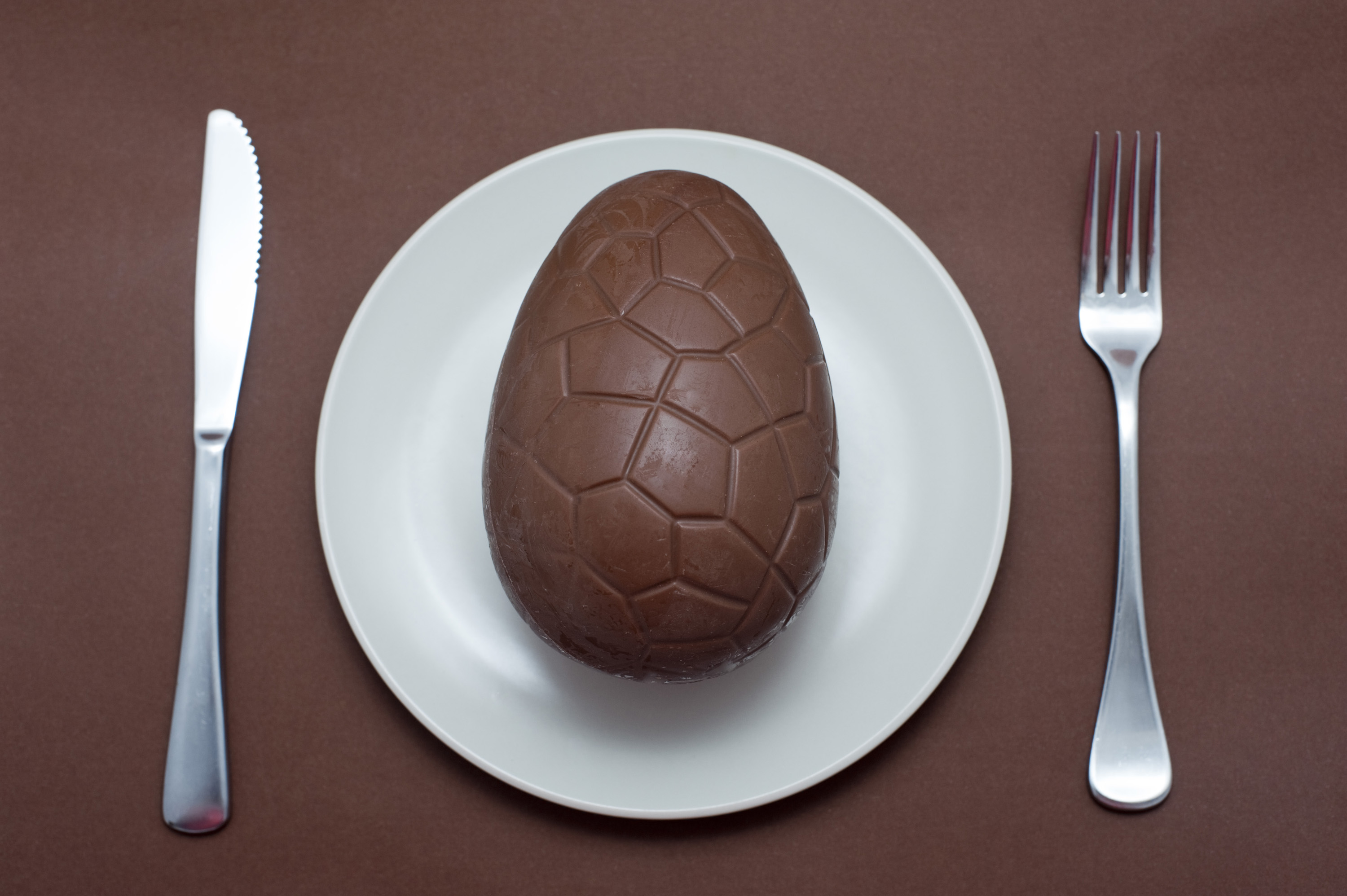 easter_egg_concept.jpg - Place setting with a chocolate Easter egg served for dinner on a plate with cutlery over a matching brown background