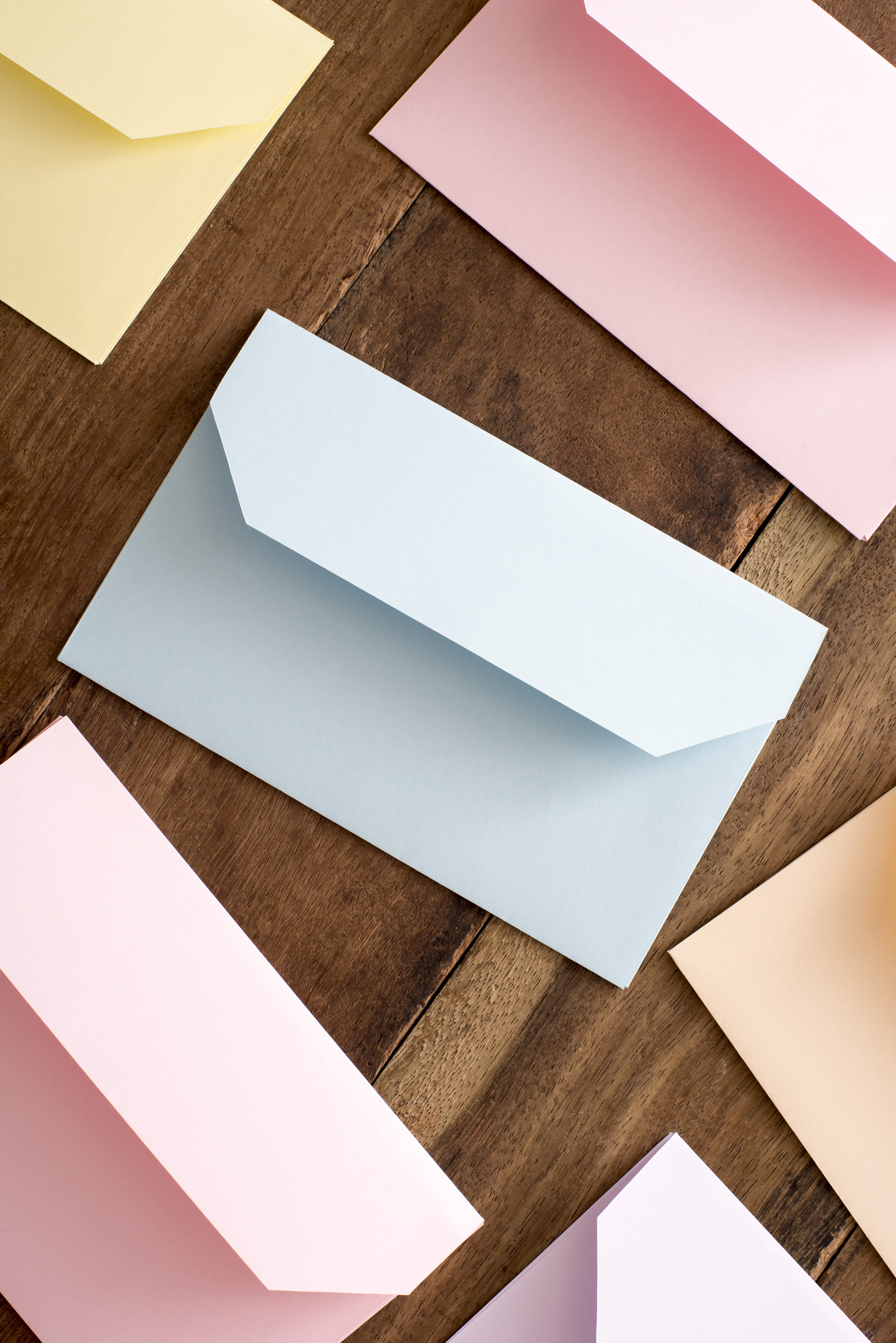 easter_greeting_opened.jpg - Top view of several open pink, blue and yellow envelopes on brown wooden surface