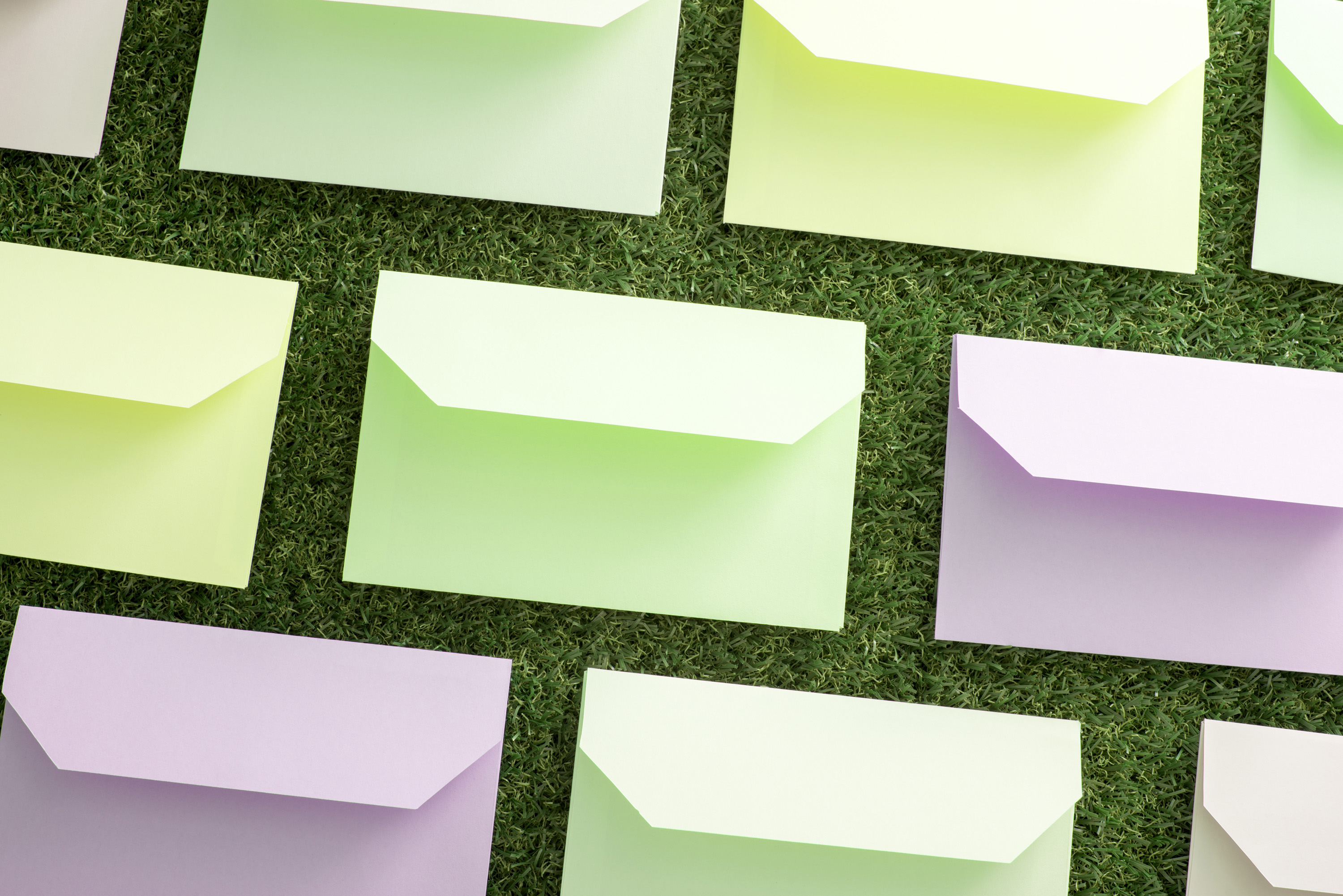 easter_spring_greeting.jpg - Rows of pastel colored envelopes neatly arranged on green grass viewed from above in a communications or correspondence concept