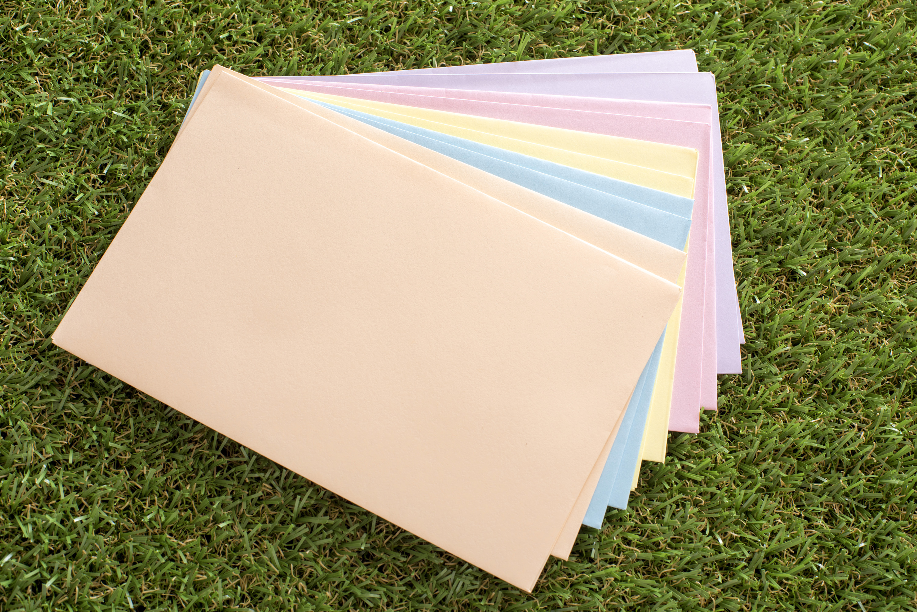 messages_for_easter.jpg - Stack of colorful unused envelopes for Easter messages lying fanned out on fresh green grass in a concept of spring and holiday celebration greetings