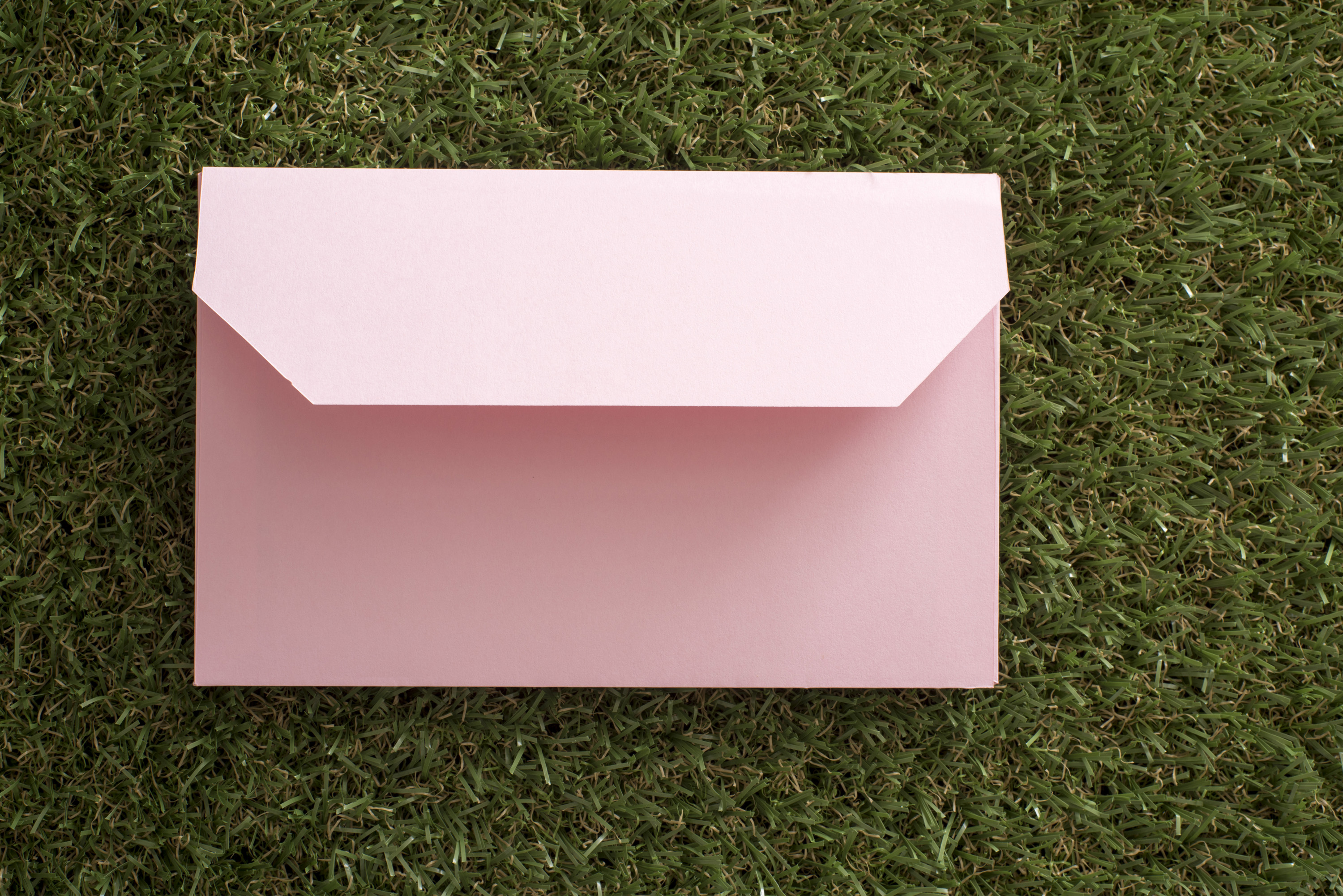opened_envelope.jpg - Single pastel pink envelope opened face down on green grass conceptual of Easter spring greetings and wishes
