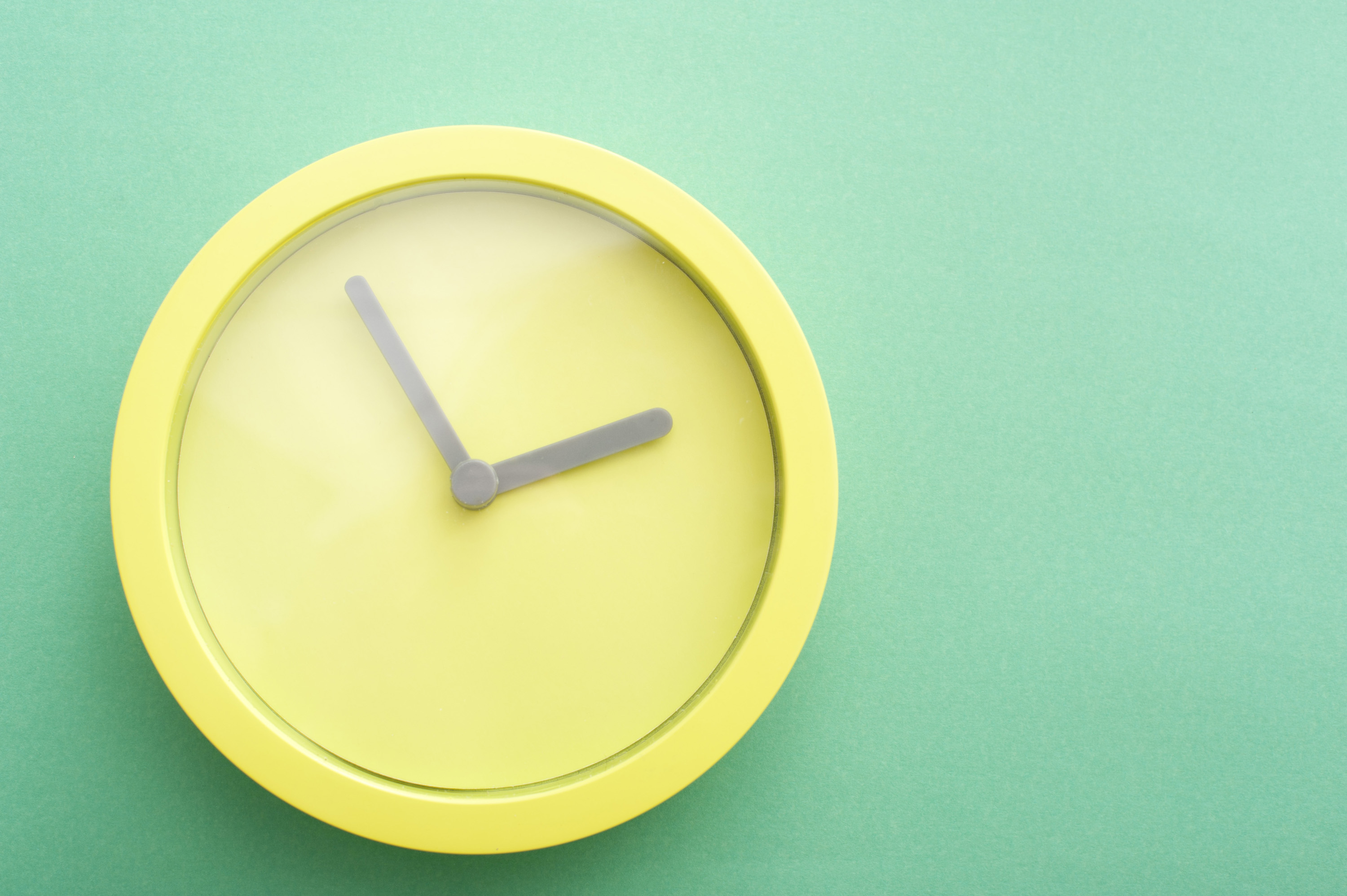 time_concept.jpg - Springtime concept: Modern minimalist yellow round clock or timer with no numbers on a green background