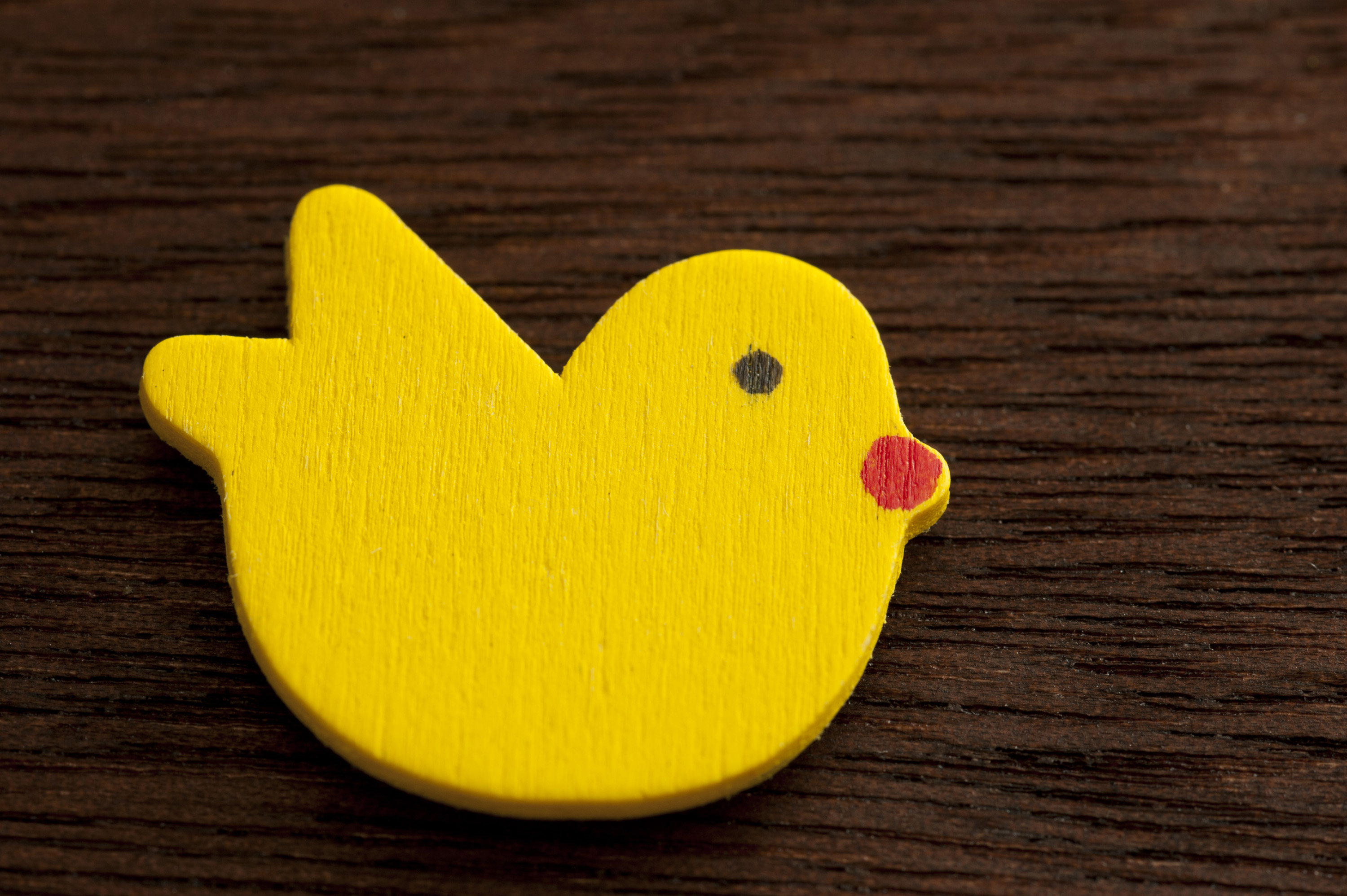 wood_easter_chick.jpg - Cut and painted wooden chick for Easter holiday. View from above over dark wood table.